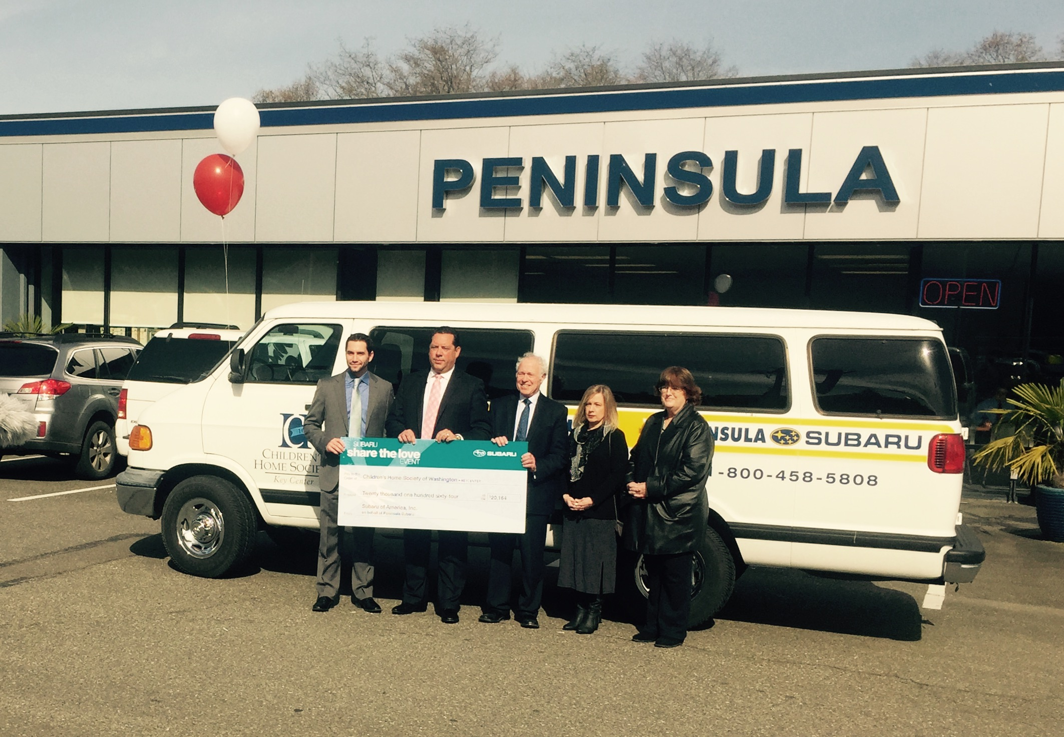 John Dionas, second from left, presents a check from the Peninsula Auto Group to Key Peninsula Family Resource Center staff.