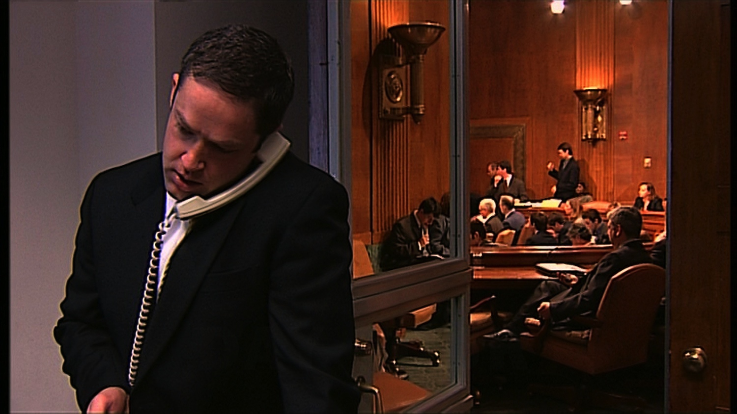 HDWN_11_HD_STILL_Doorway Hearing Room_Staffer on Phone 02.jpeg
