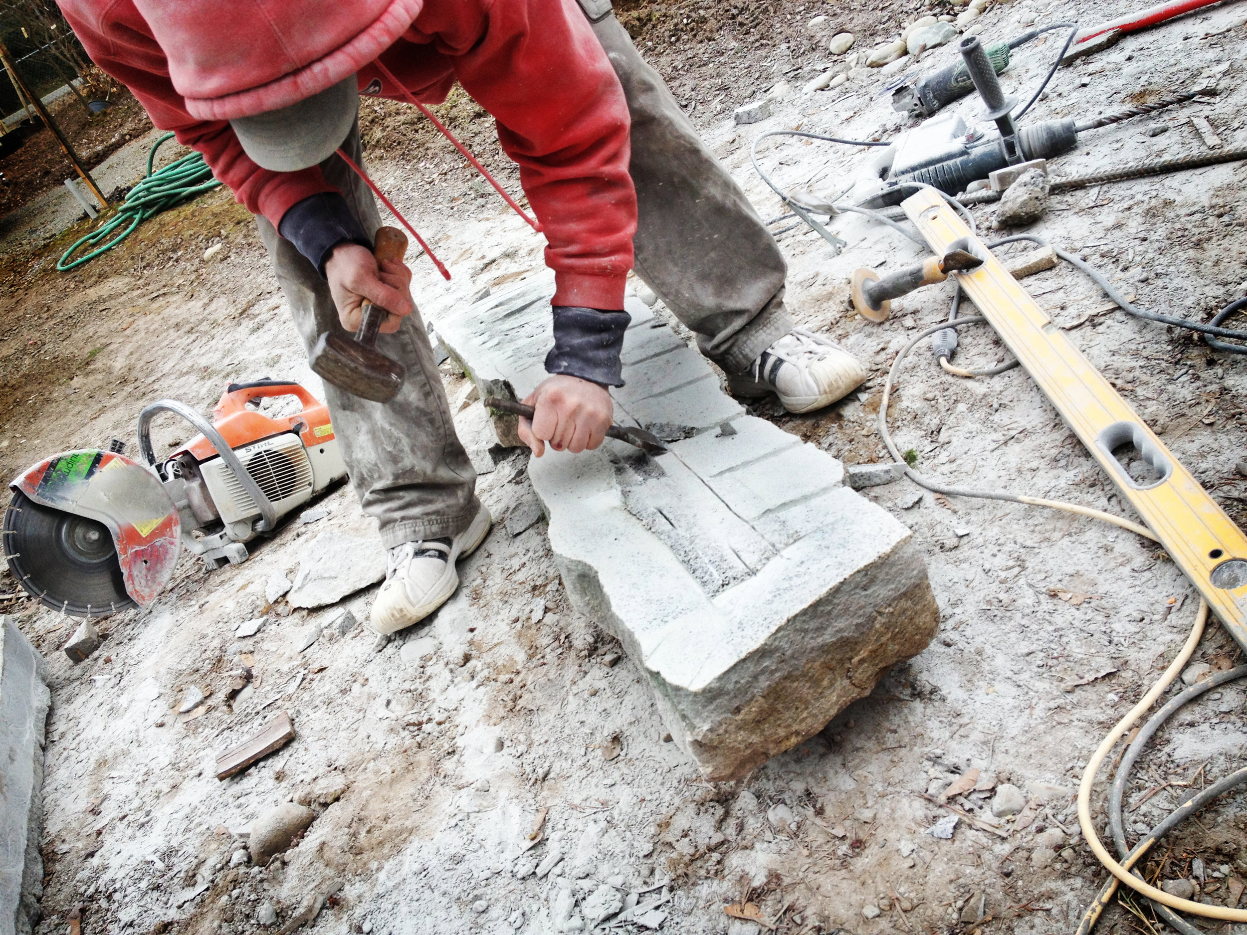 Chiseling and crafting a perfect piece of granite to create the mantle for the grand rock fireplace. ..