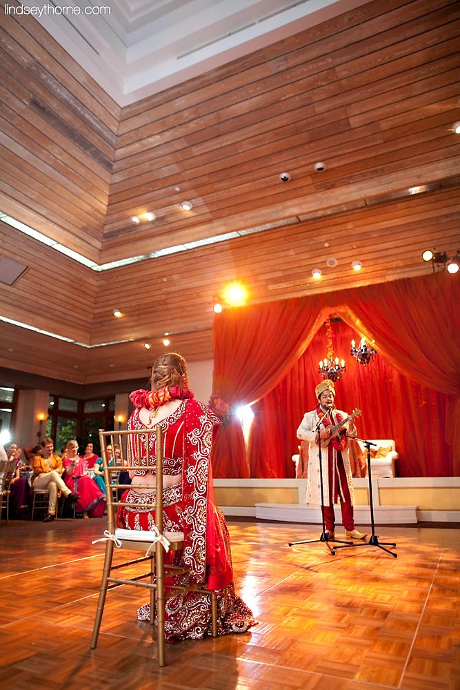 grooms sings song to bride in ballroom celebration