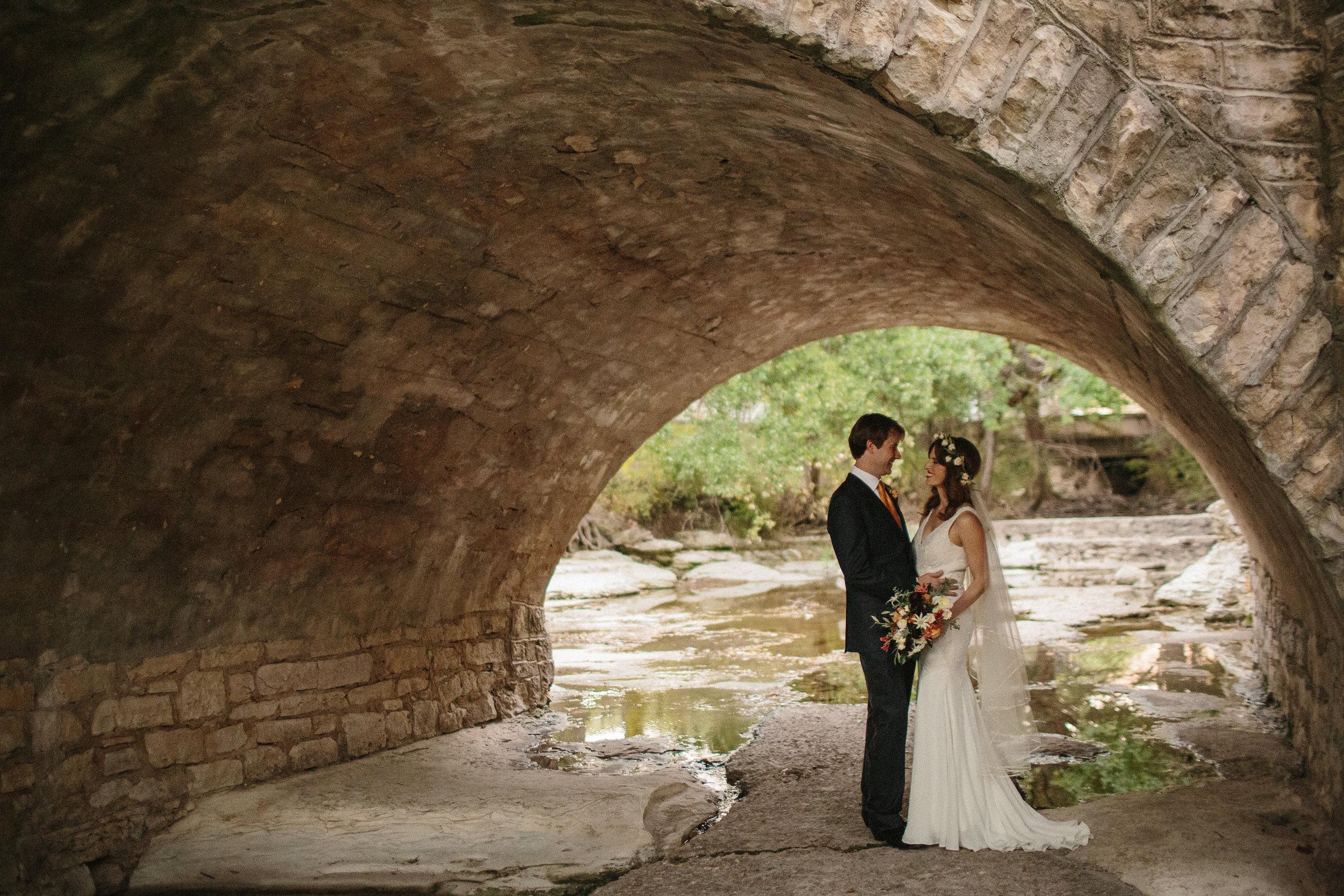 bride and groom under bridge by waller creek