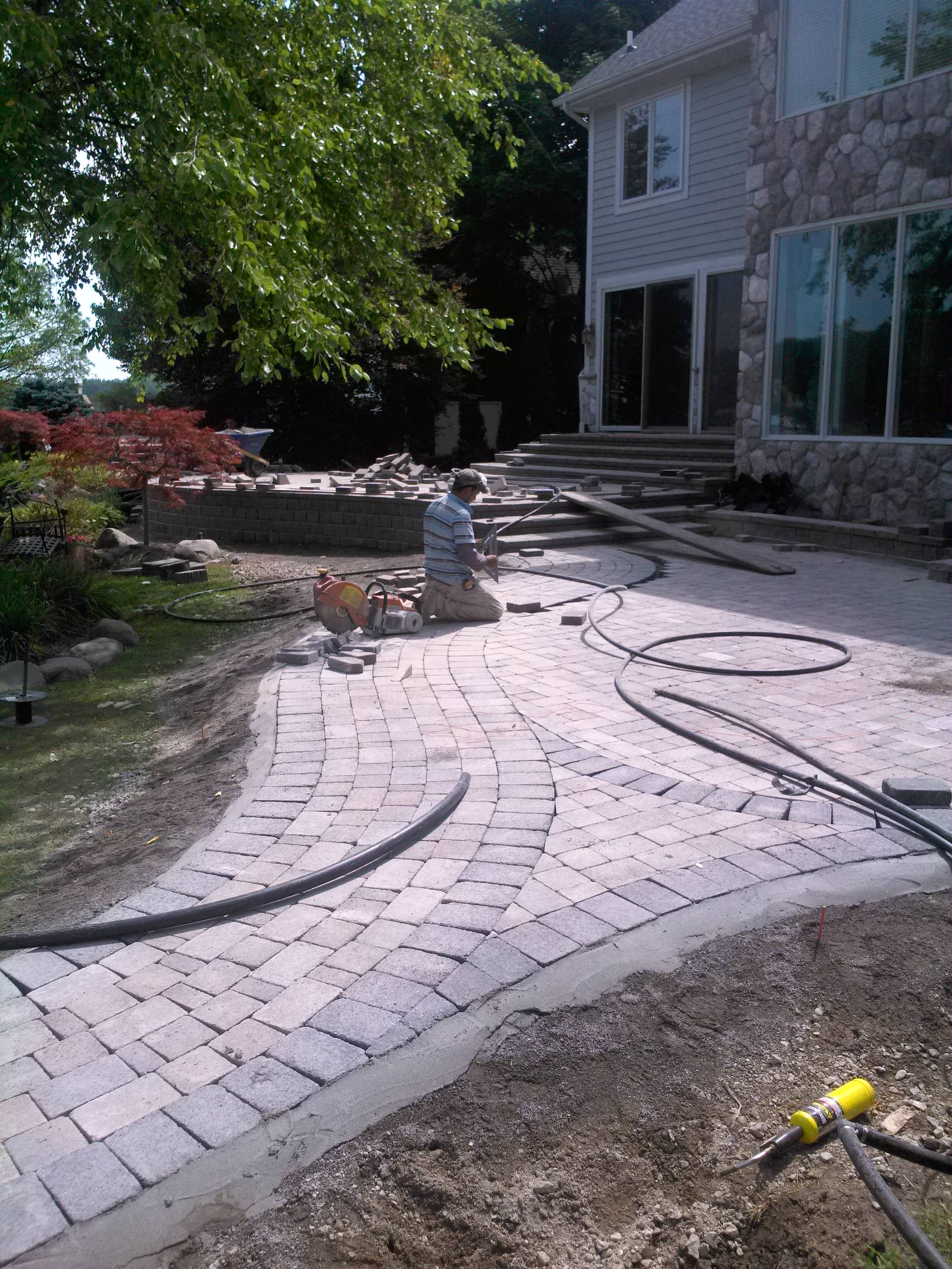 One of our experienced team members laying down brick pavers in the back yard of a long time customer.