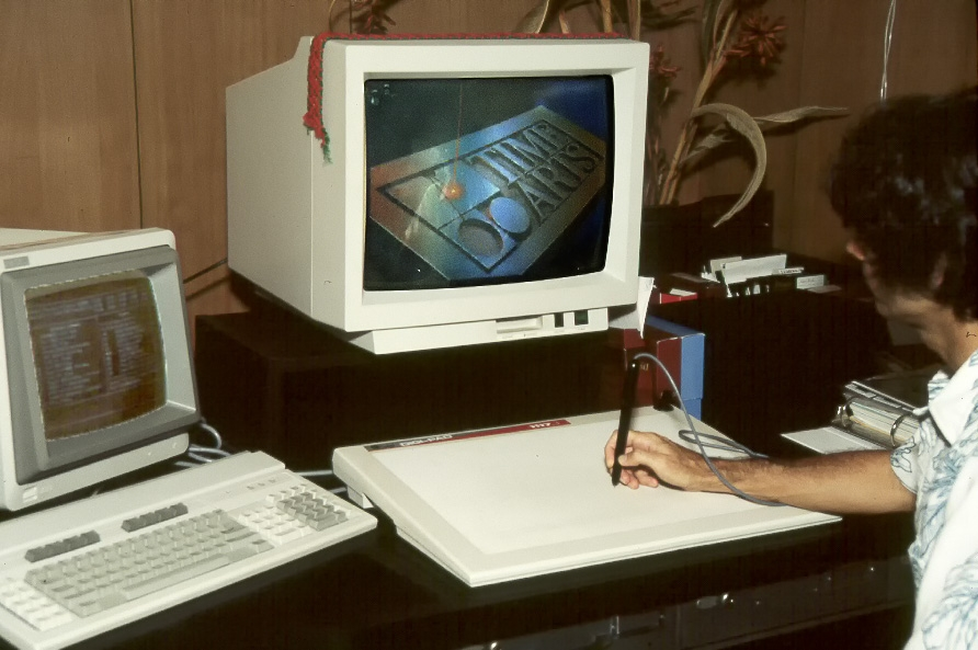 Sitting at a Lumena-9 workstation. an ibm pc with a special graphics board drove the color monitor. Note the size of the monitor, both in terms of screen size (nobody had screens that big) and bulk of the monitor (it was very heavy). input used a digitizing tablet and pc keyboard. 256 colors (of your choice). the screen image is a splash screen, not an image drawn in the lab.