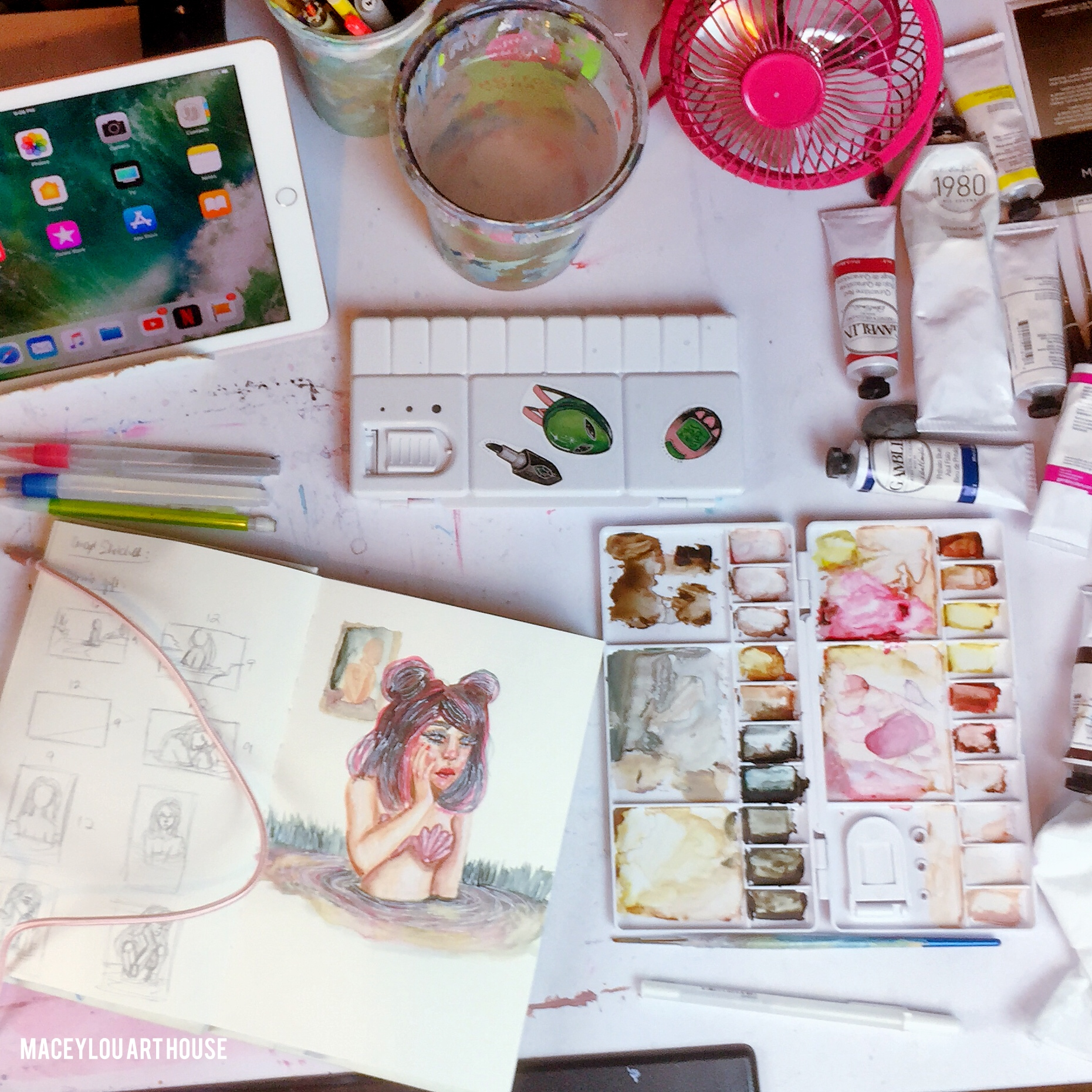 messy art studio desk with ipad and watercolor sketchbook