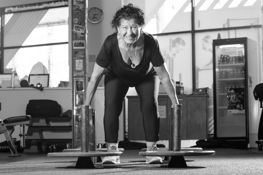senior lady lifting heavy weights in gym