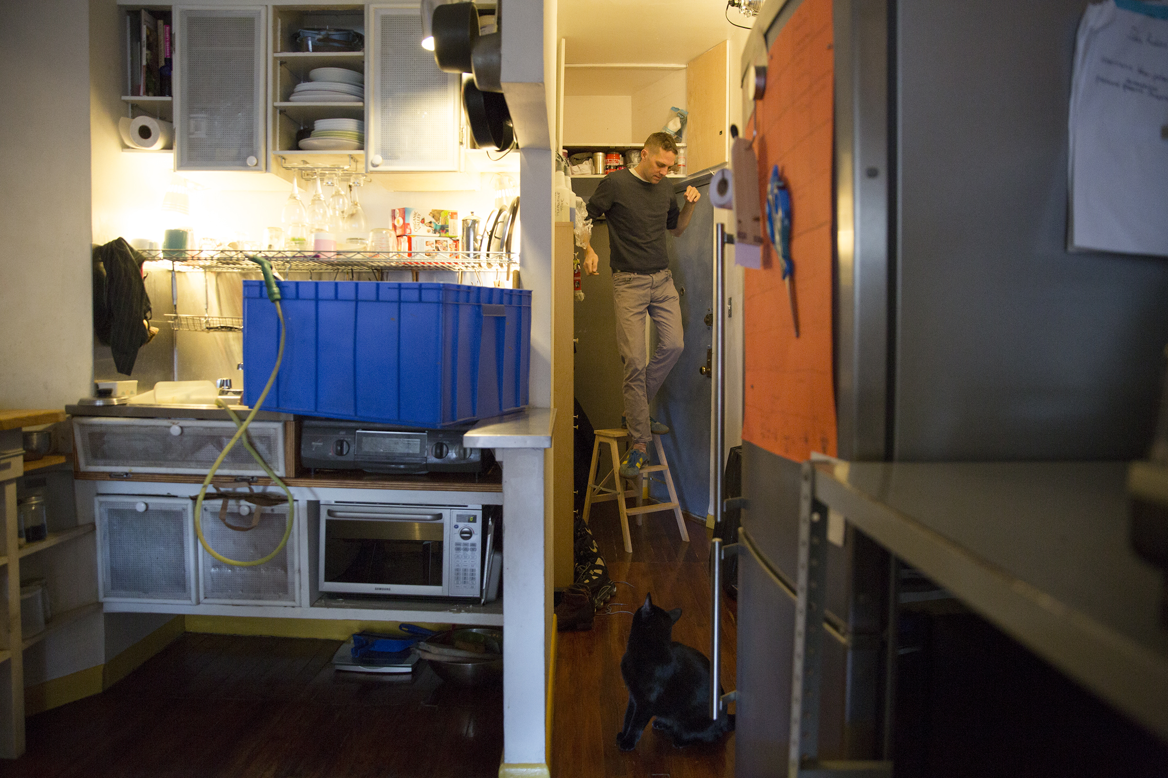 A blue storage bin doubles as a washing station, set up on the sink where Anselm has custom fit a rubber hose to fill it. He is in the back, getting supplies stored in a nook above his daughter's room.