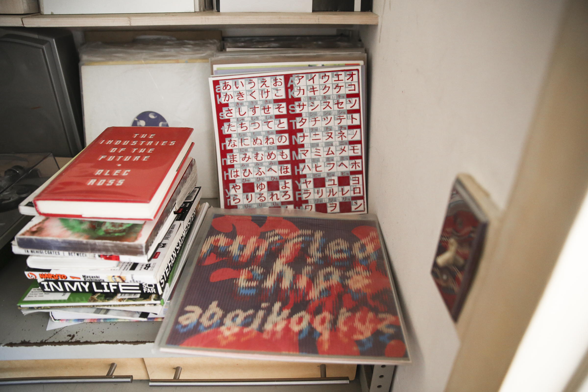 "The finished versions ""ruffled chips"" and the Japanese language typography silkscreens near Anselm's music station. A stack of library books waiting to be returned stands to the left."