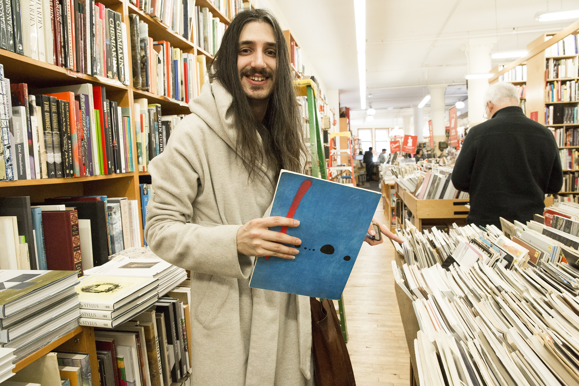 "Aaron browses the used book section. The Joan Miró ""Blue"" painting on back cover of the book they're holding happens to be a poster in their room."