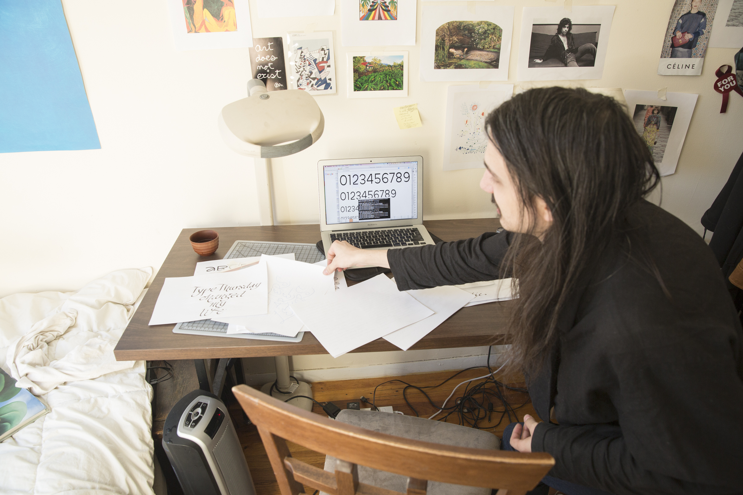 Aaron goes through calligraphy exercises and type sketches. A typeface they're working on is visible on the computer screen. They studied under type master Tony DiSpigna, who was a big influence on their calligraphic style.