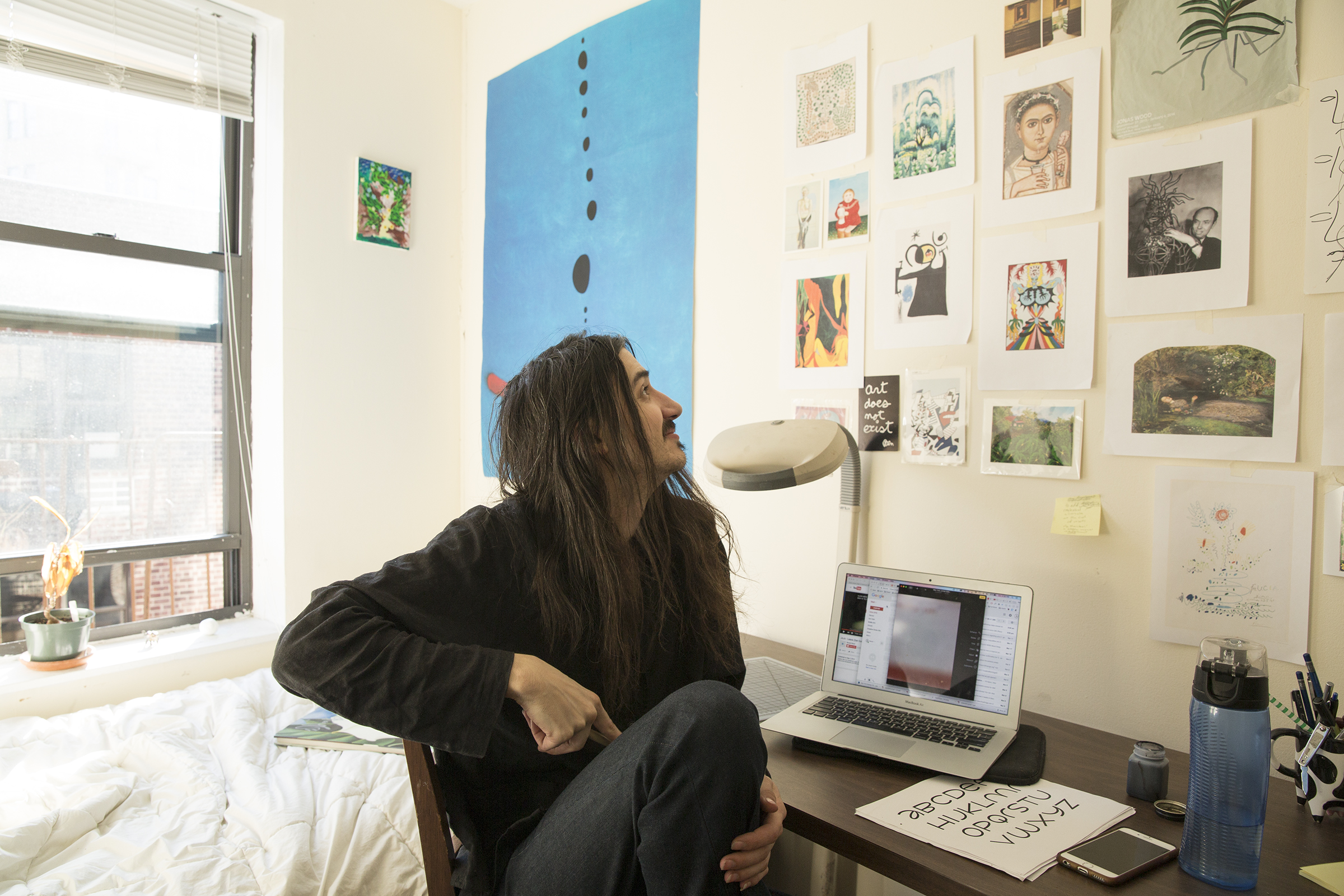 "Aaron sits in their room at home in the West Village where they share a small apartment with a roommate. The wall is covered in artworks and ephemera that inspire them or relate to a project they're working on. Note the Joan Miró ""Blue"" poster on the wall, the same painting they found on a book in The Strand."