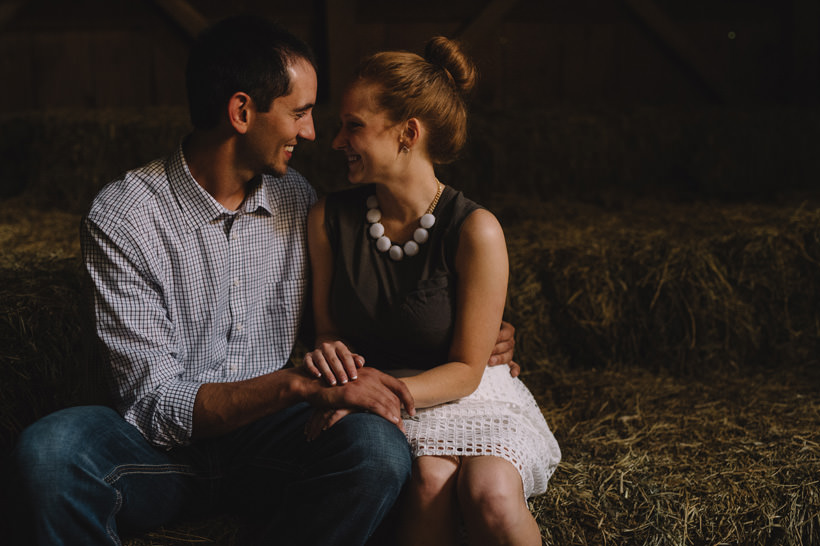 Erin and Scott look at each other in the attic of a rustic barn