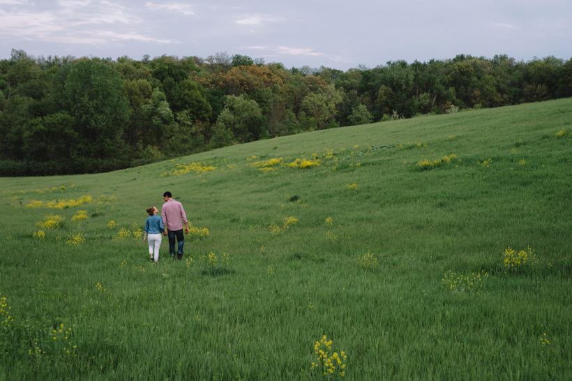 Erin and Scott stroll through a beautiful field