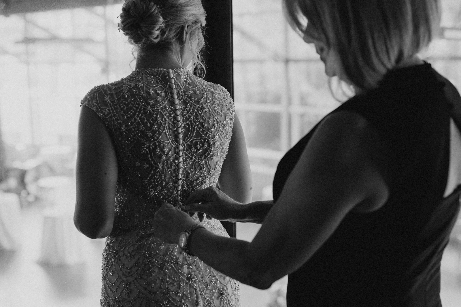 A stepfather watches as his daughter gets into her wedding dress | Iowa Wedding Photographer Brian Davis