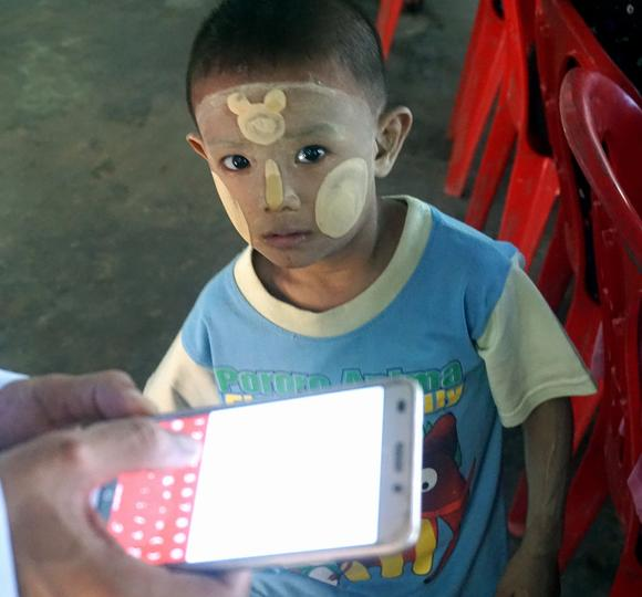 Like children everywhere, this Burmese boy can't get enough of his parents' mobile telephone. (Photo by Denis D. Gray)