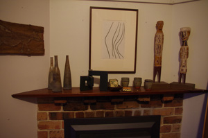 7 Margaret Tuckson AM 1921 – 2014: Jennifer Isaacs   Margaret Tuckson's mantlepiece with Gwyn Hanssen Pigott bottles at left, Tony Tuckson's framed drawing, and at right Yirrkala carved and painted figures from their trip in 1959; photo: Jennifer Isaacs