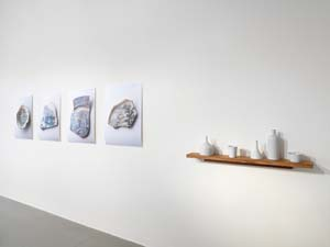 7 Build me a city I Cry me a river: LISA HARMS   Kirsten Coehlo, foreground:  oil can, cup, funnel, bottle, bowl , 2012, porcelain objects, dimensions variable (tallest 28cm); background:  Dreams of Leaving , 2012; four photographs on photographic paper of ceramic shards from new Royal Adelaide Hospital site, North Terrace; SA Museum collection; 80 x 60cm each; image courtesy the artist, Helen Gory Gallery, Melbourne, and BMGArt, Adelaide