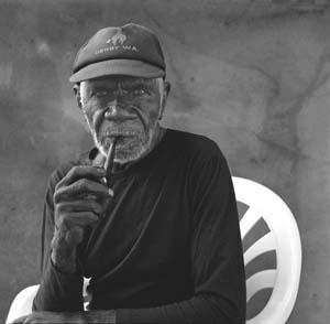 11 Ngarra, Andinyin/Kitja Artist, c.1920 to 2008: HENRY F. SKERRITT   Ngarra at home in Derby, 2002. This photograph was taken by Ngarra's long-time friend and facilitator Kevin Shaw, and appears in Shaw's publication  Mates: Images and Stories from the Kimberley,  Australian Scholarly Publishing, Melbourne 2002. Ngarra approved of his photographic image being used after his death