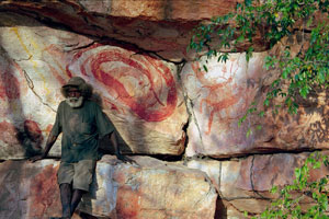 4 Rarrk – John Mawurndjul: A journey through time in northern Australia: MELINDA HINKSON   John Mawurndjul beside a rock painting of Ngalyod, Dilebang, Arnhem Land, Northern Territory, September 2004. Photo Erika Koch