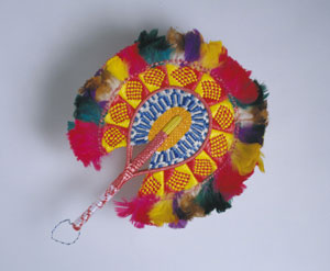 7 Craft + design. What's in a name?: IAN WERE   Vaisamoa Manoa,  Fan , 2003, woven raffia over coconut midrib, dyed feathers. Courtesy of the Queensland Art Gallery.   8 The day the art world came to Balgo: JACQUELINE HEALY   At  Balgo 4-04 : Philomena Baadjo and her family in the exhibition, Helicopter Tjungurrayi in the background. Courtesy of Warlayirti Artiists. Photo Kim Lawler.