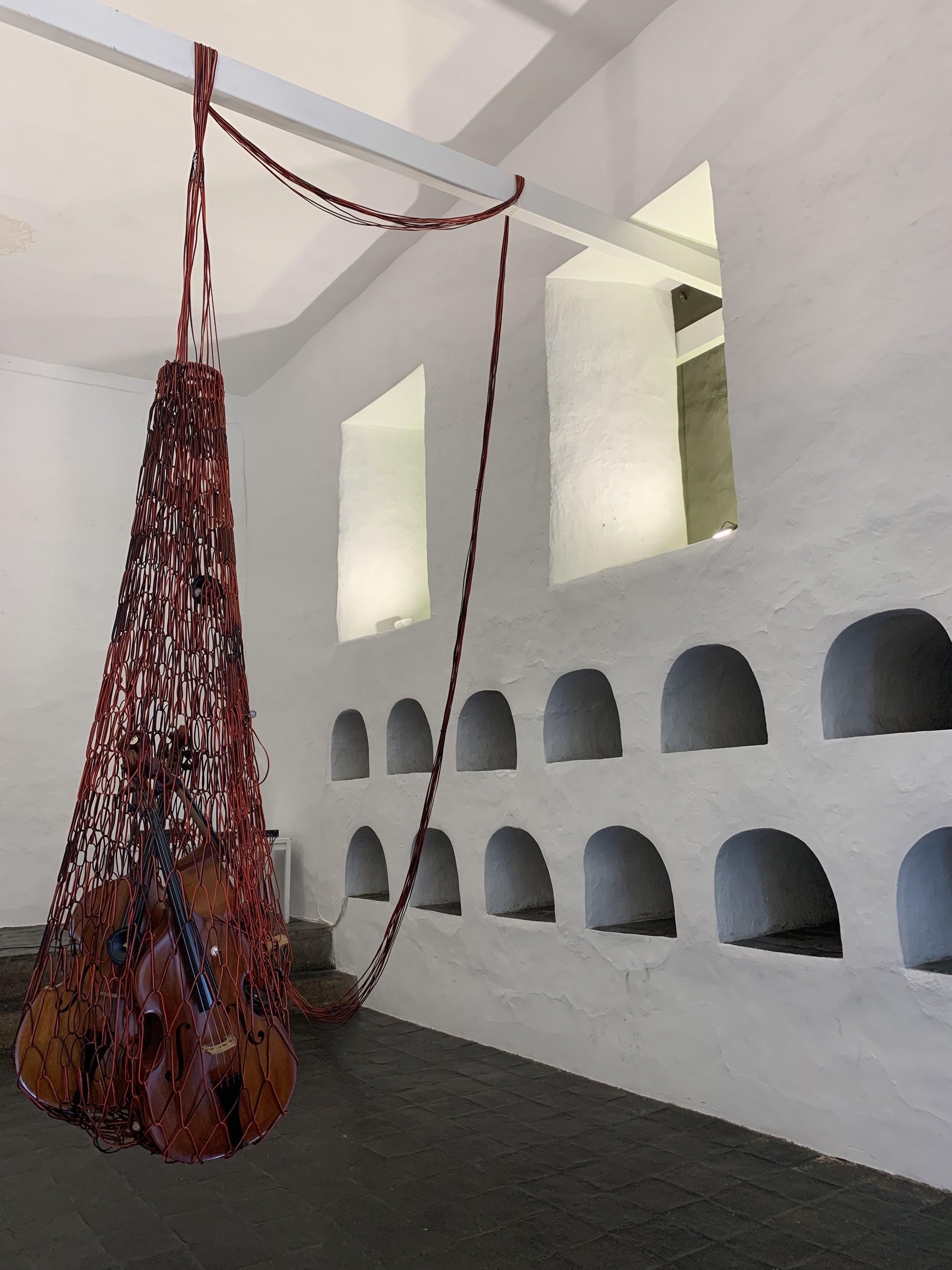 Cecilia López,  Red , 2018, installation view, Museo del Monasterio de las Conceptas, 14th Cuenca Biennial, 2018; audio cables, double basses, stereo; photo: Natalia Ottolenghi Bradshaw