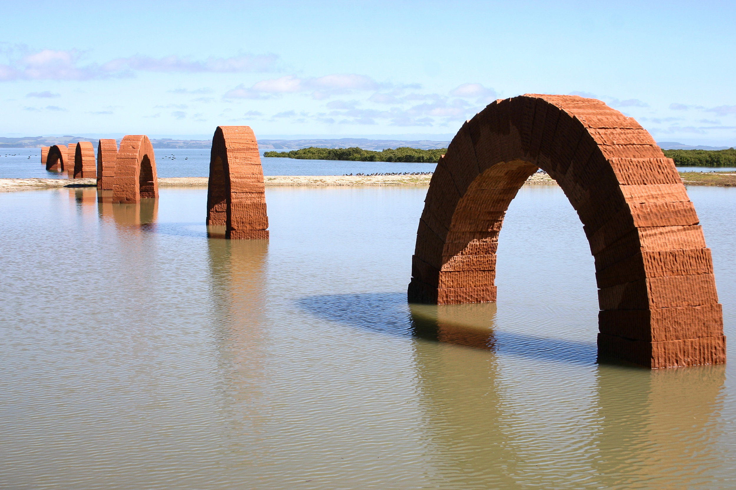 5 Hard, clear light reveals the bones'; visiting the gibbs farm; Patrick hutchings,  kaipara harbour    Andy Goldsworthy,  Arches , 2005, pink Leadhills sandstone blocks stacked into 11 freestanding arches (each 7m long); image courtesy Gibbs Farm,   Kaipara Harbour