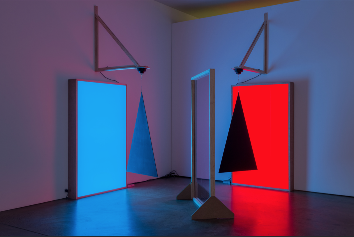 5 TAREE MACKENZIE'S CARTESIAN UTOPIA: PARIS LETTAU AND AMELIA WINATA   Taree Mackenzie,  Pepper's ghost, triangles, cyan and red , 2018, acrylic, MDF, reflective tint, LEDs, mirror-ball motor, paint, wood, vinyl; lightbox elements: 200 x 120 x 20cm; reflective screen:200 x 120 x 7cm; hanging sculpture: 140 x 87cm; brackets: 120 x 120cm; courtesy the artist and Neon Parc, Melbourne; photo: Christo Crocker