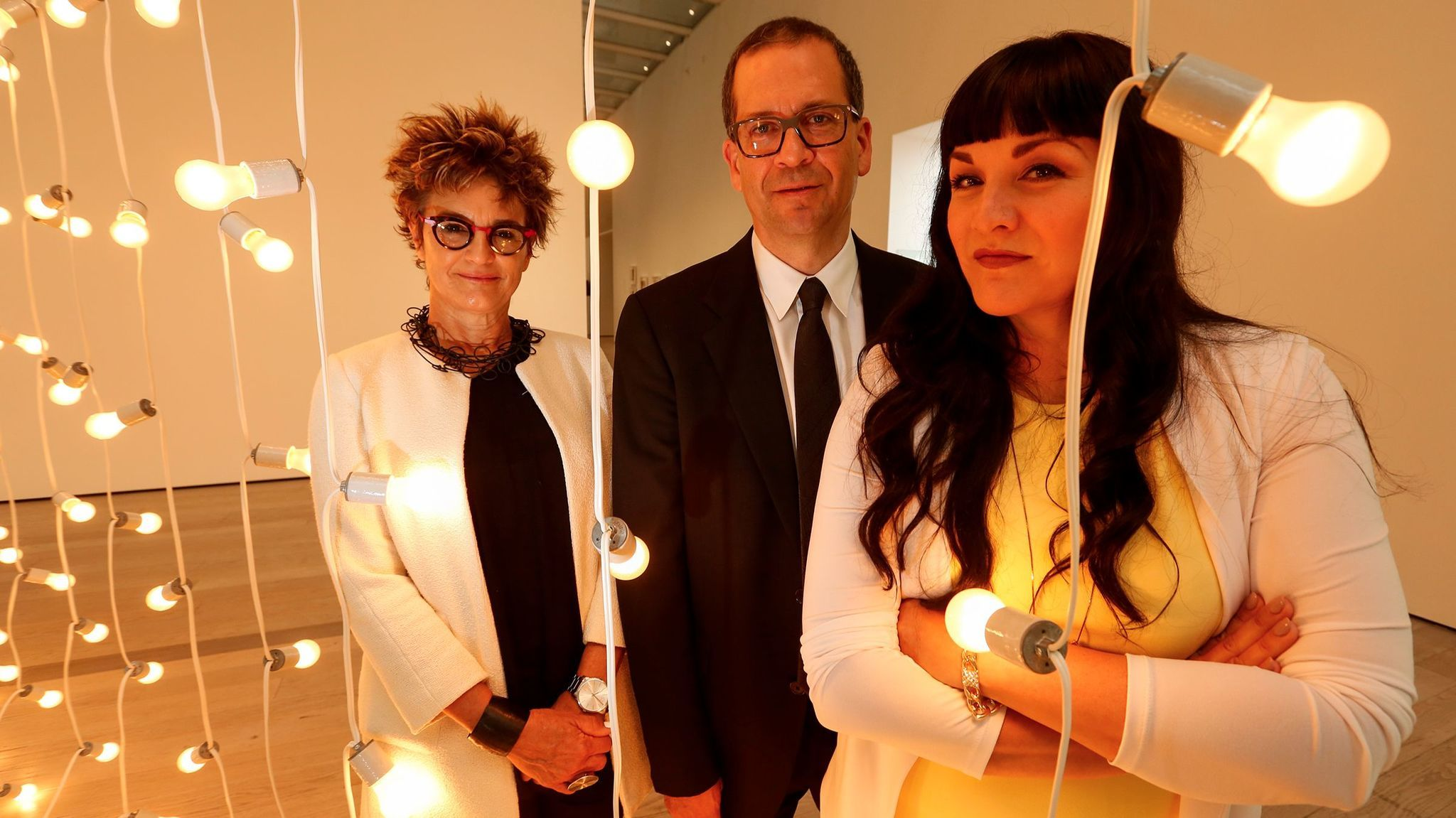"""HOME: So Different, So Appealing curators Mari Carmen Rameríz, Chon A. Noriega and Pilar Thompkins Rivas standing next to an installation by the late Felix Gonzalez-Torres, """"Untitled (North)"""" 1993. (Mark Boster/Los Angeles Times)"""