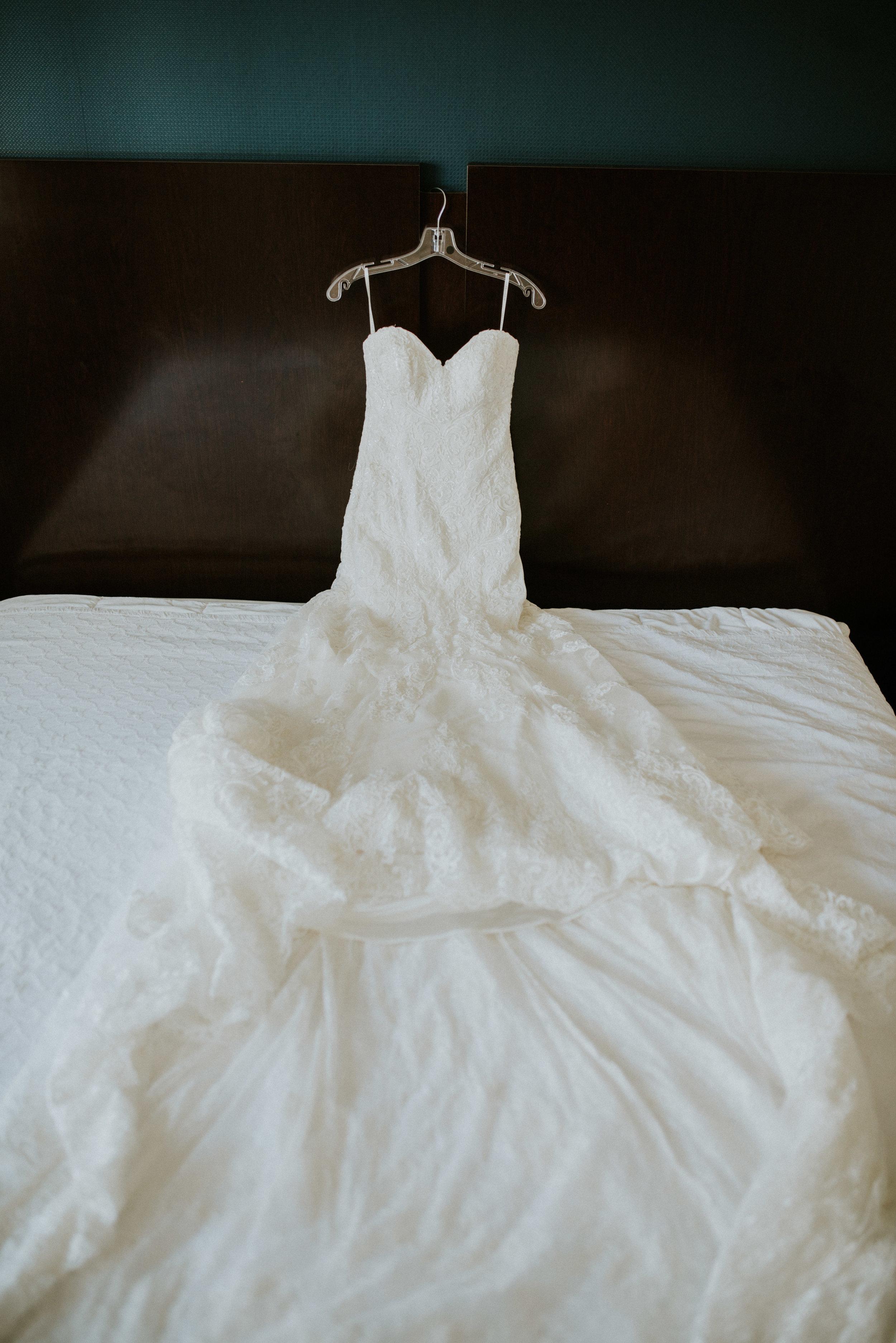 Martina Liana wedding dress draped over bed