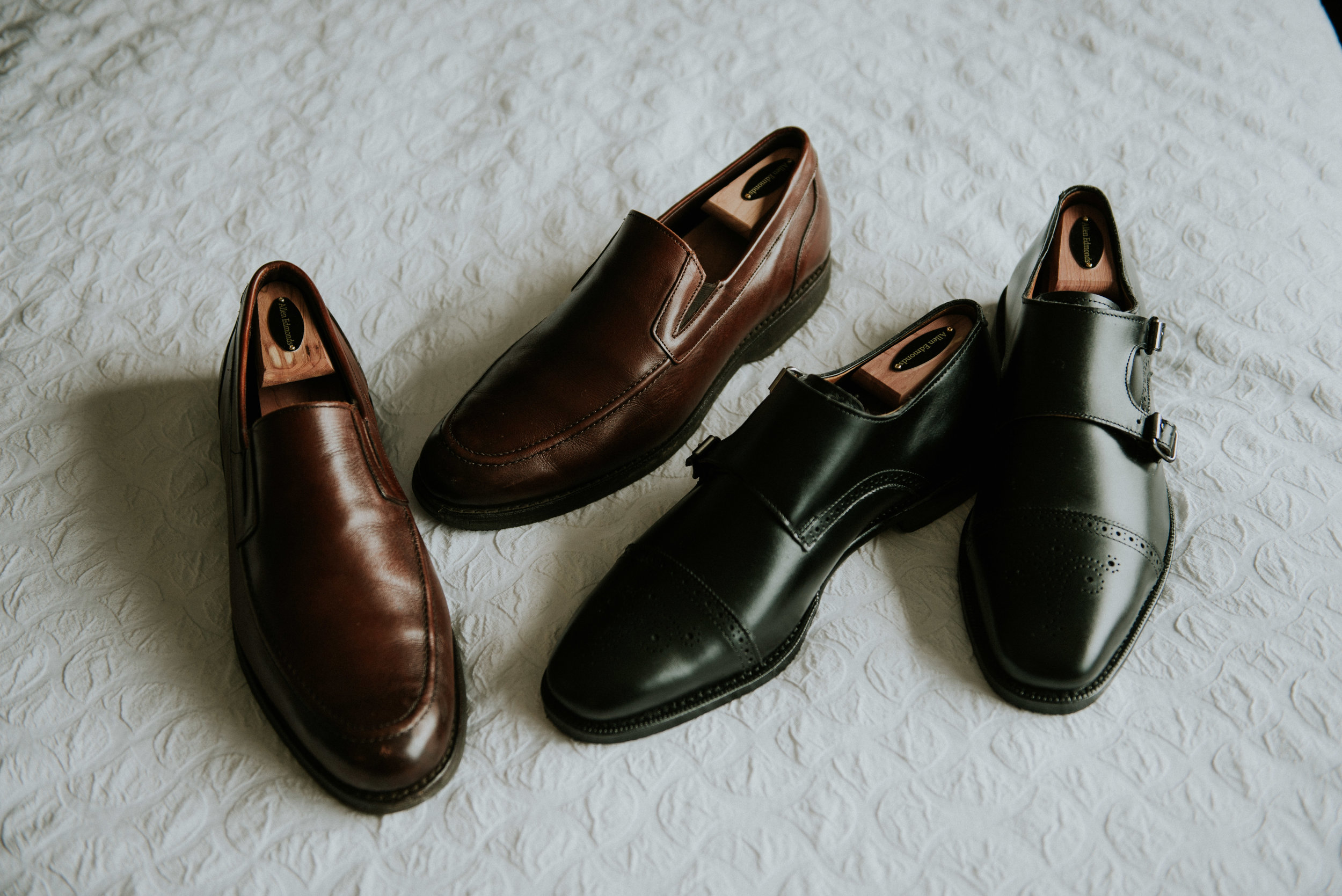 Two pairs of Allen Edmonds dress shoes scattered on a bed