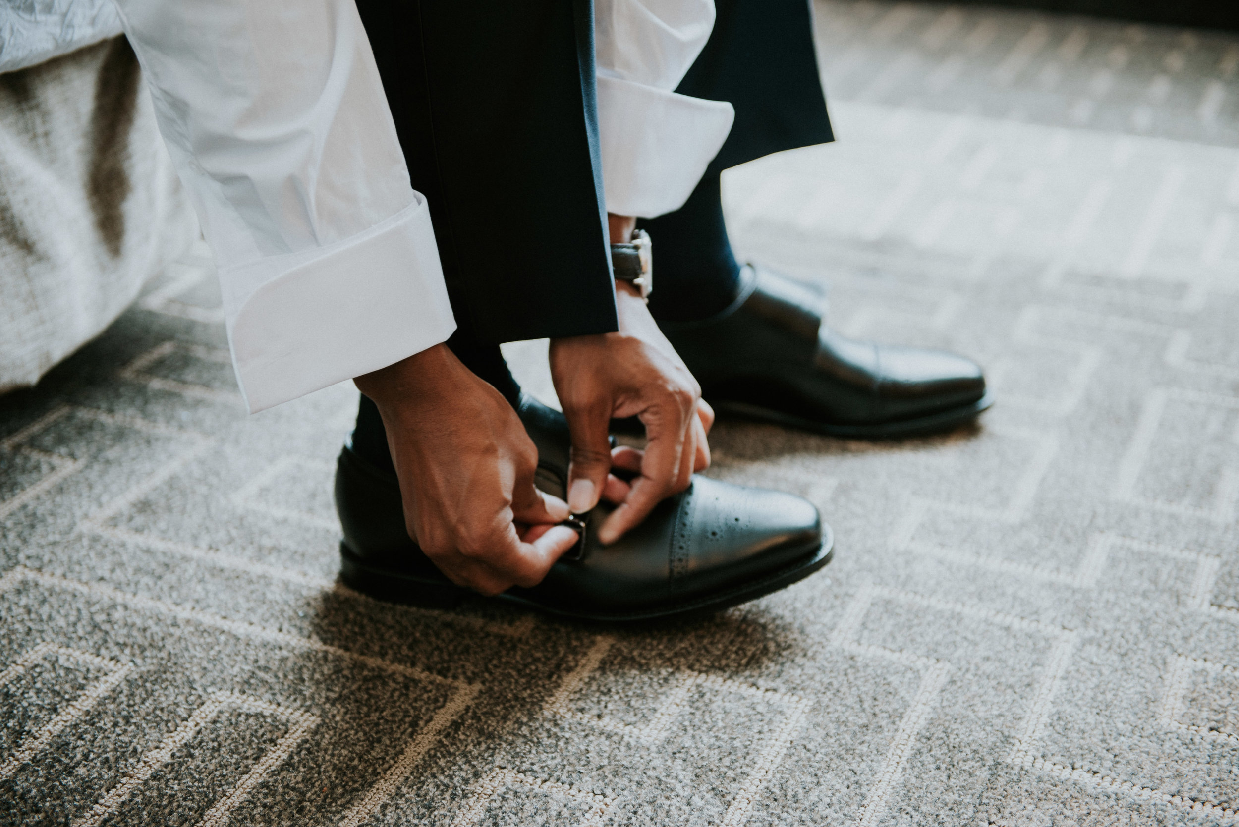 Groom lacing up his dress shoes