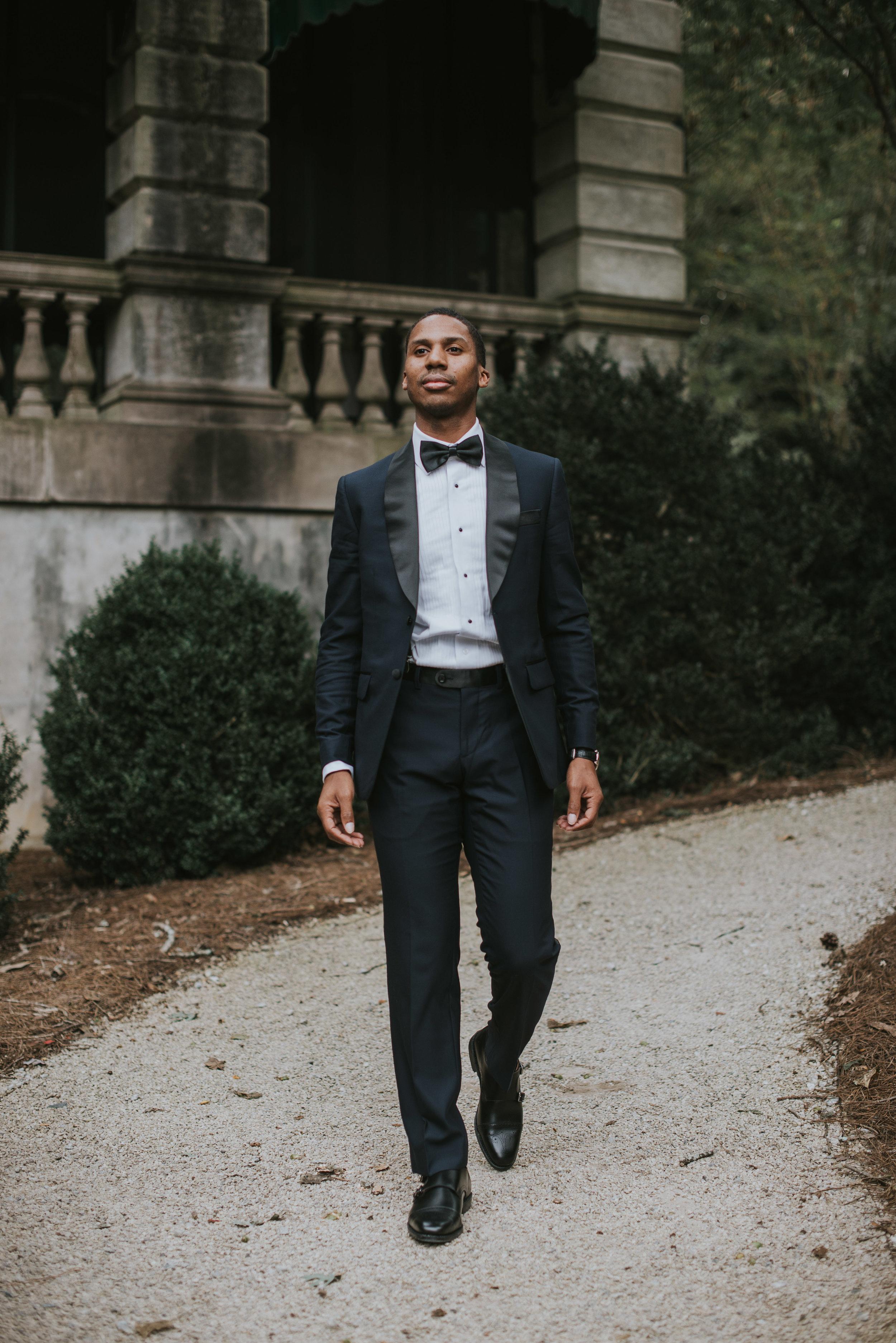Groom walking in navy Indochino tuxedo at Swan House in Atlanta, GA