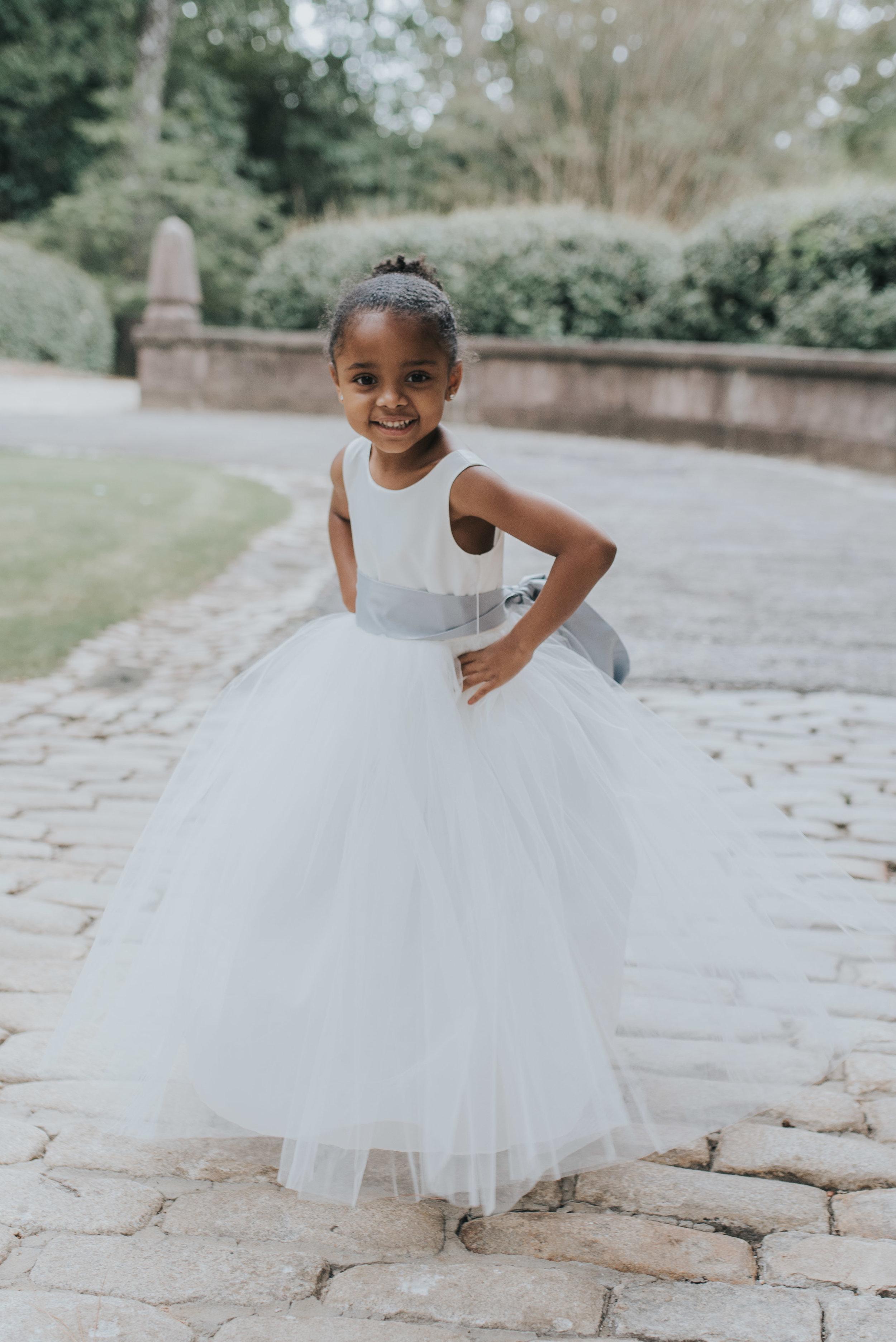 Flower girl posing before wedding ceremony at Swan House in Atlanta, GA