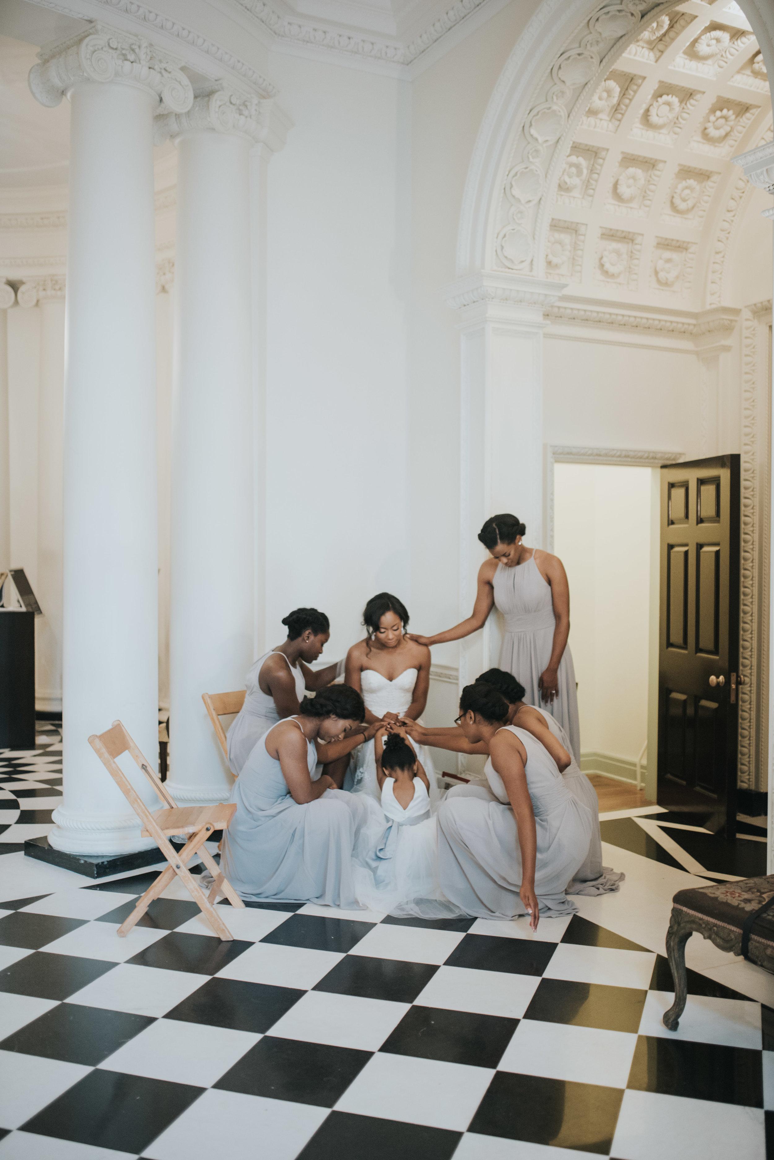 Bridesmaids pray over bride inside Swan House in Atlanta, GA