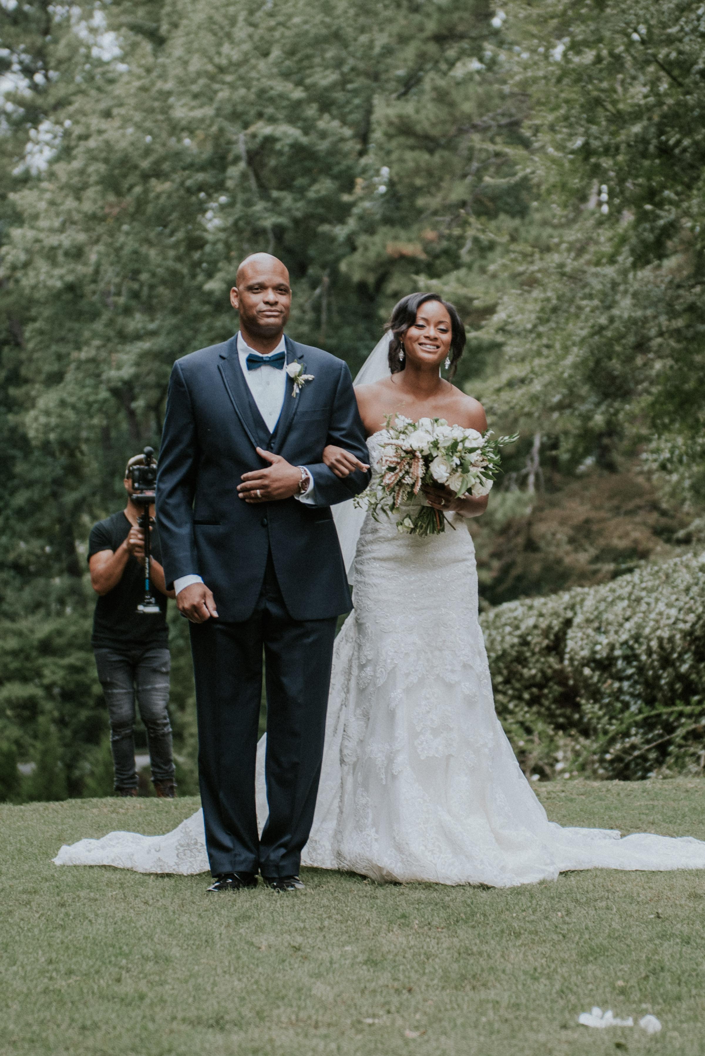 Bride smiling walking down the aisle at Swan House in Atlanta, GA