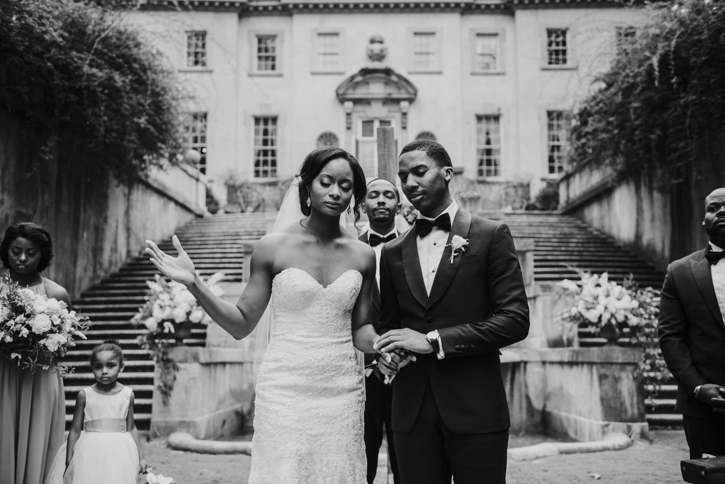 Bride and groom pray at Swan House wedding ceremony in Atlanta, GA
