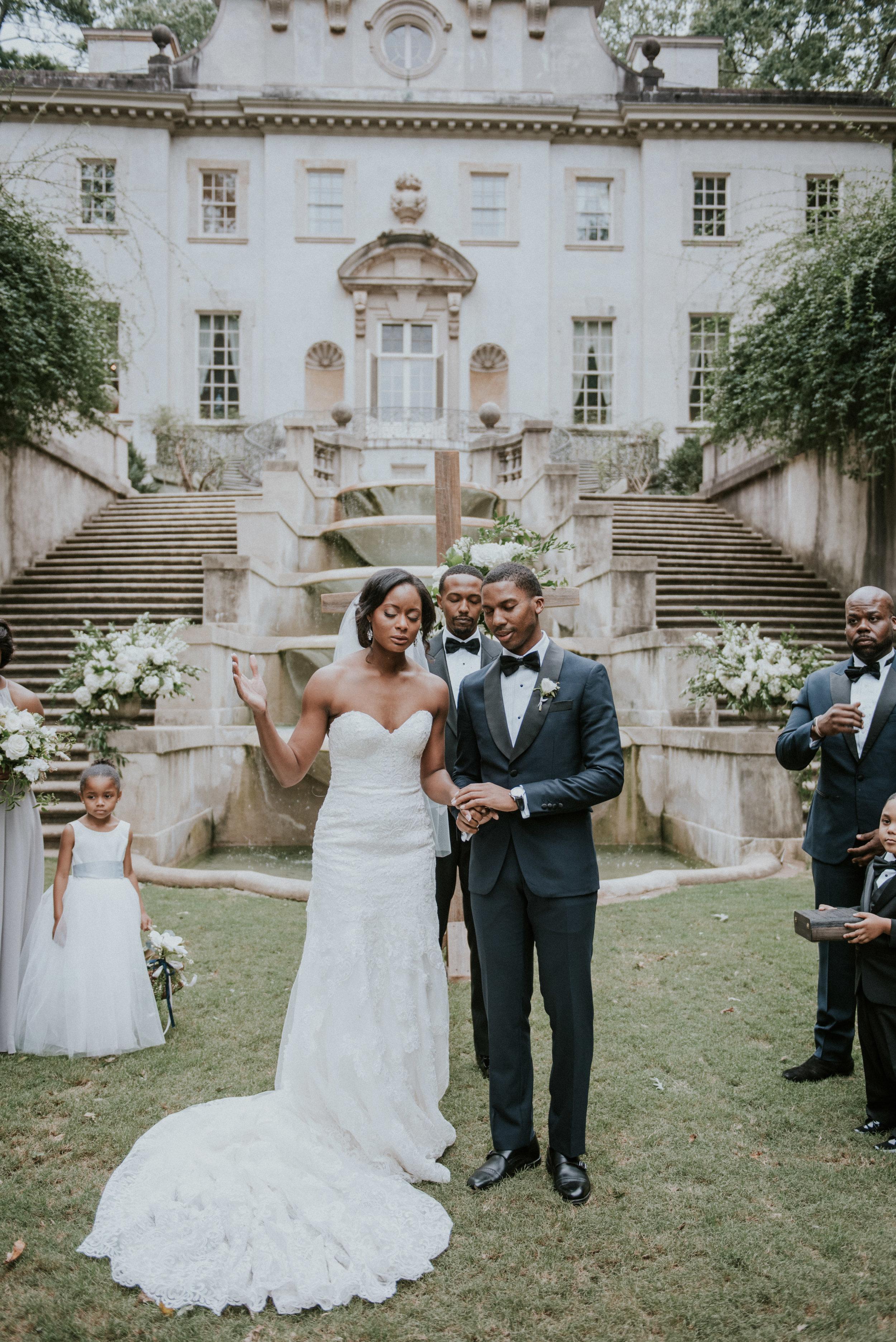 Bride and groom pray at wedding ceremony