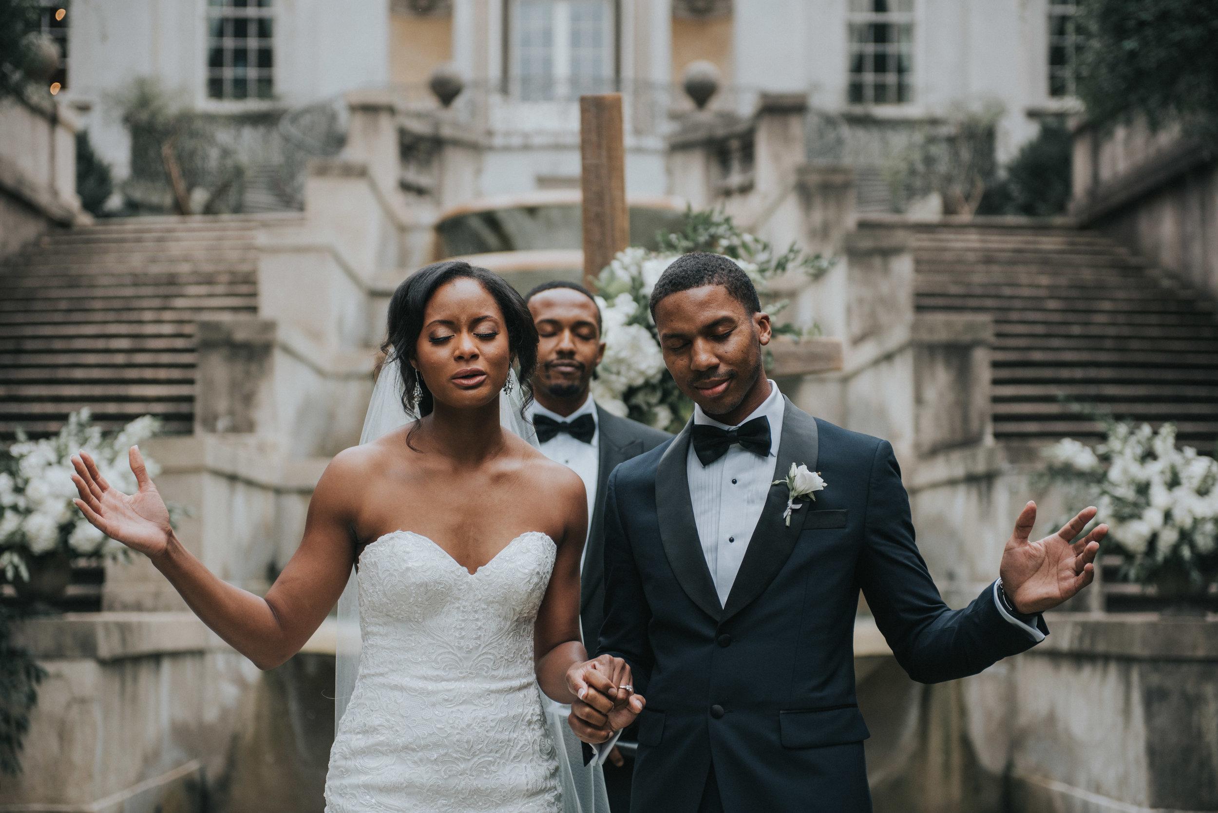 Bride and groom worship during wedding ceremony at  Swan House in Atlanta, GA