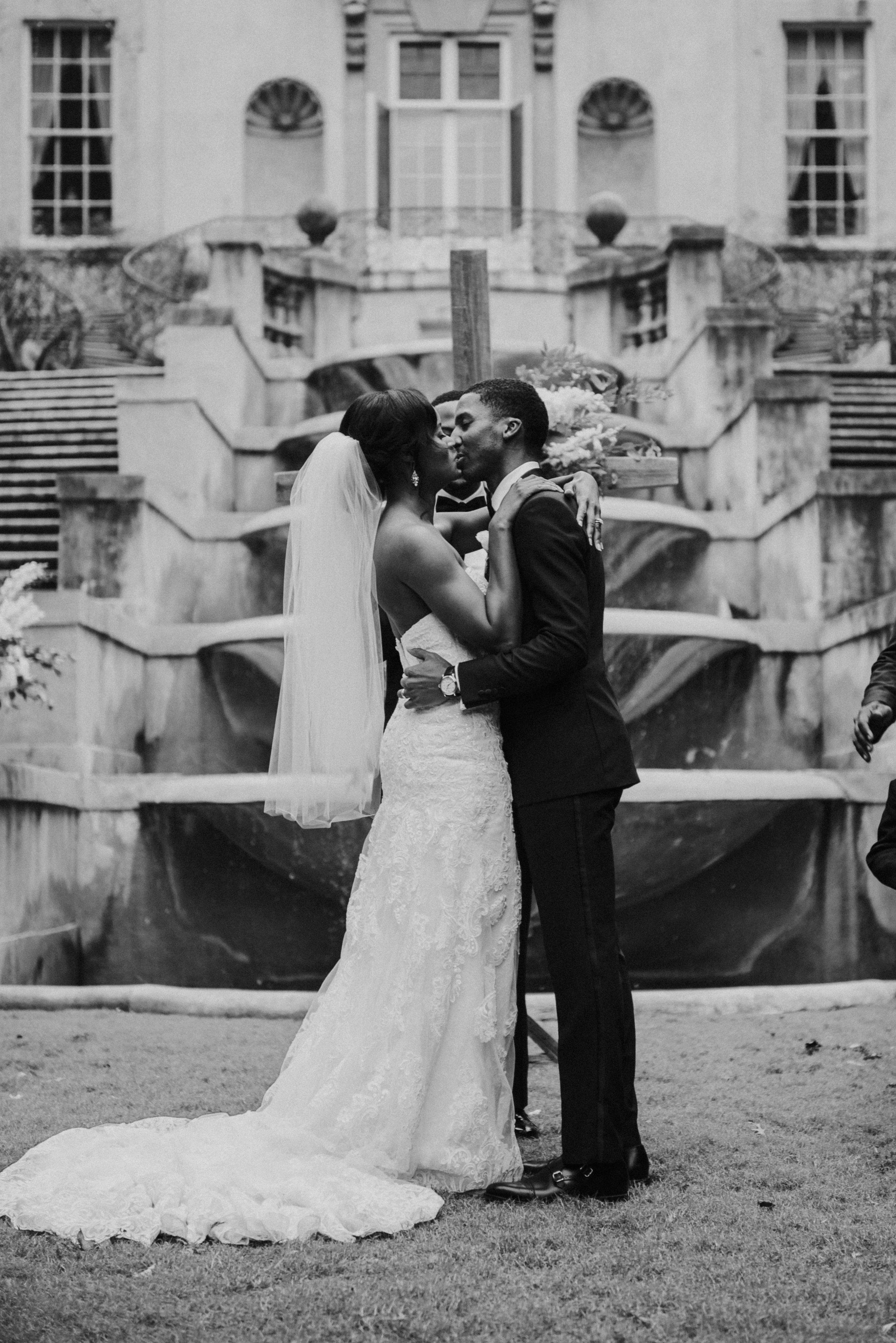 Bride and groom kiss at wedding ceremony at Swan House in Atlanta, GA