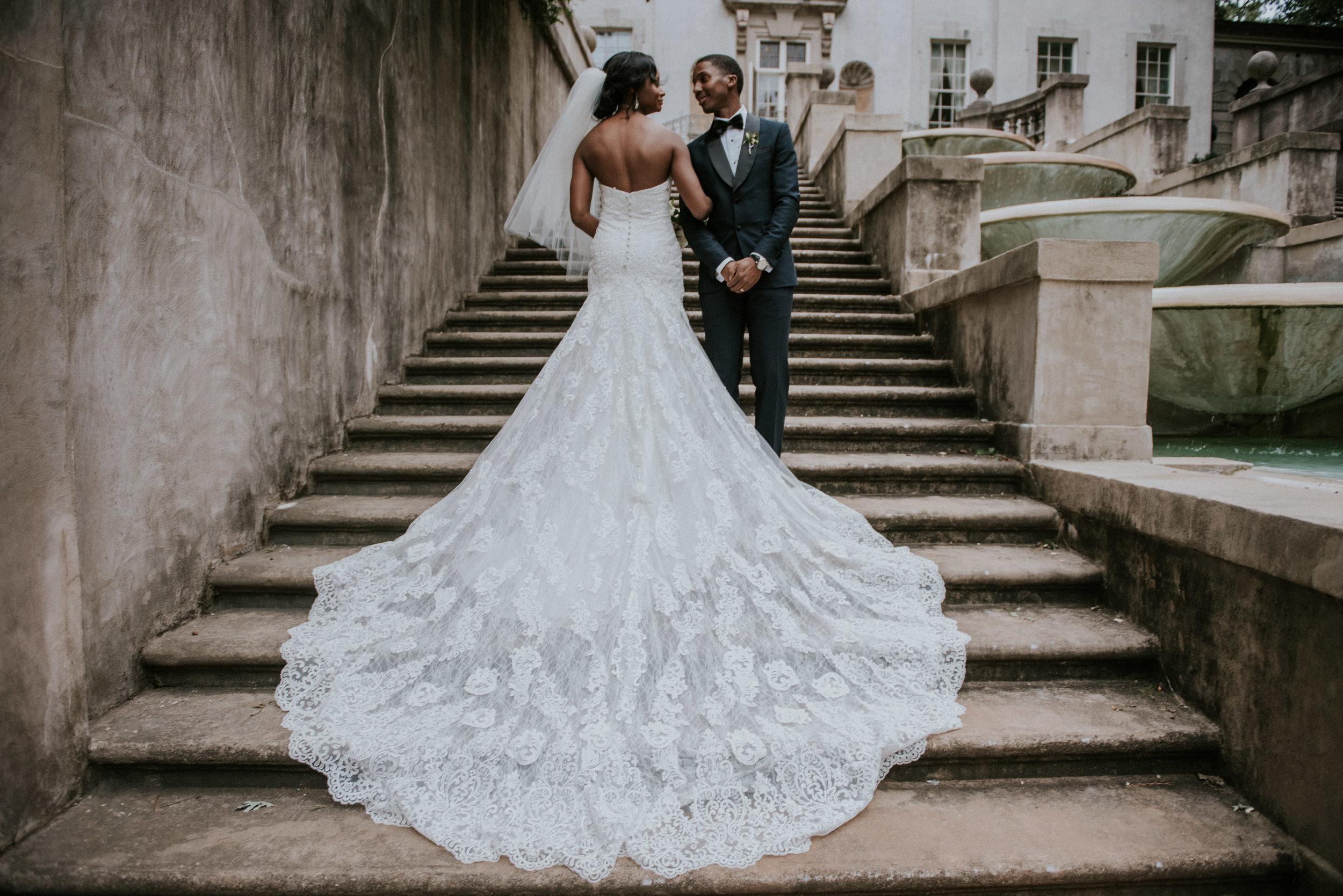 Bride and groom with Martina Liana dress cascading over Swan House steps