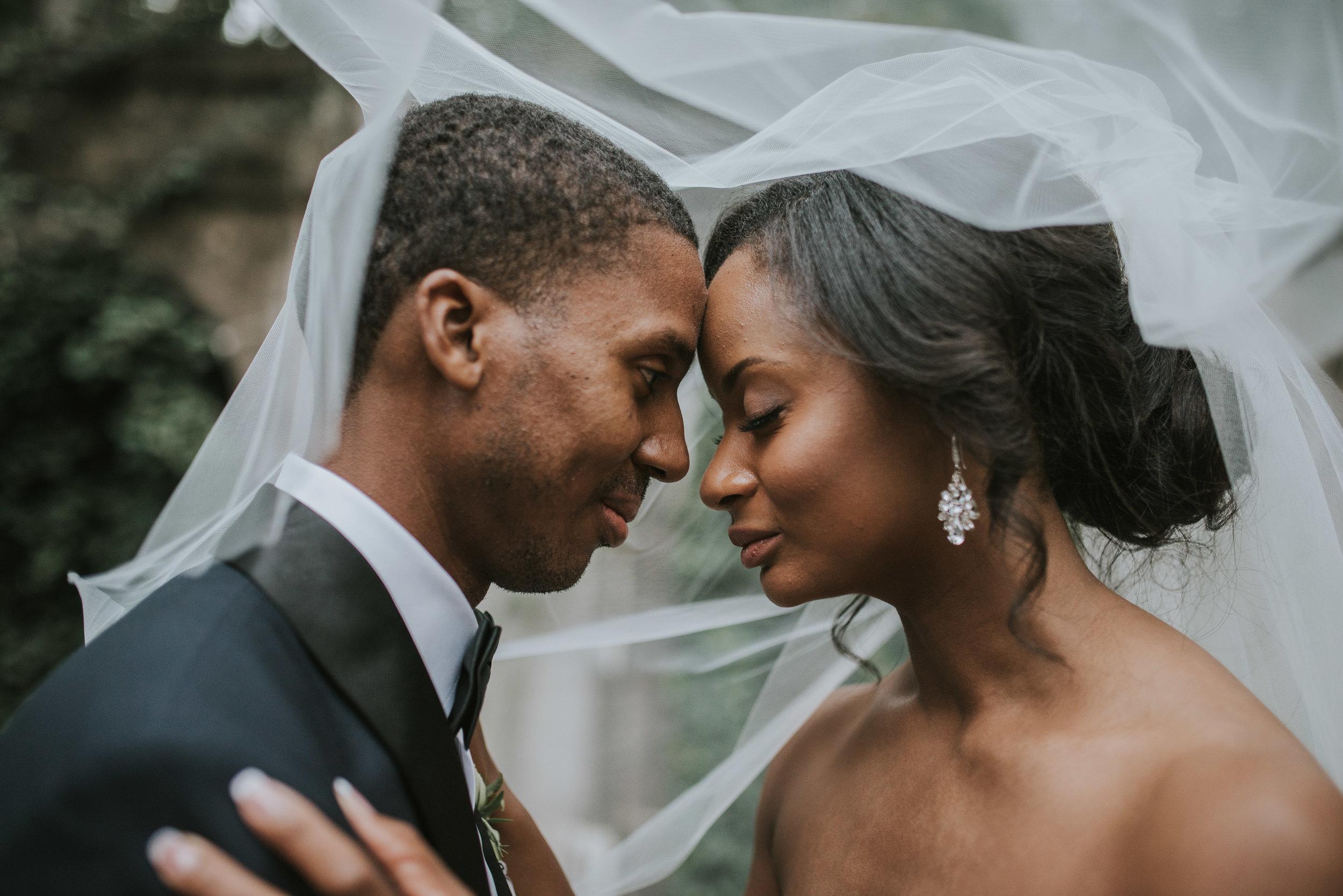 Bride and groom intimate underneath veil