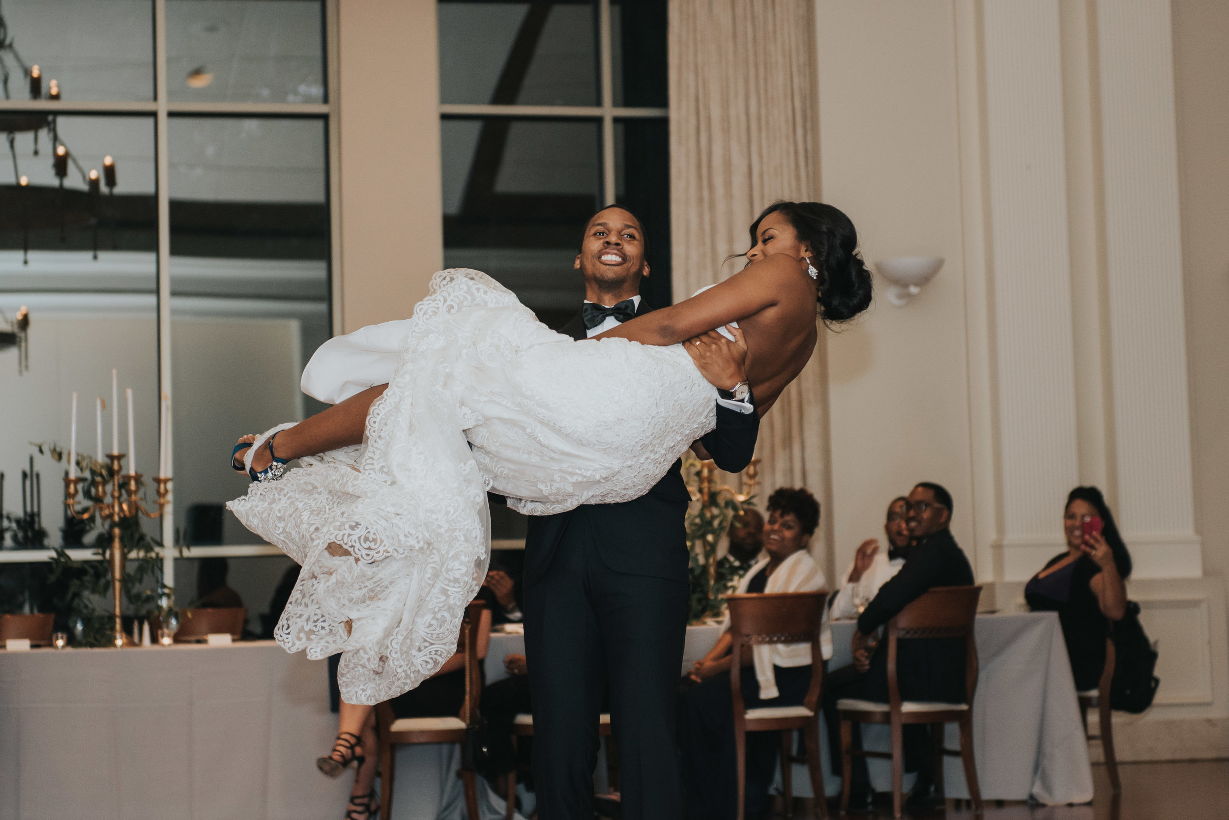 Groom carrying bride at wedding reception