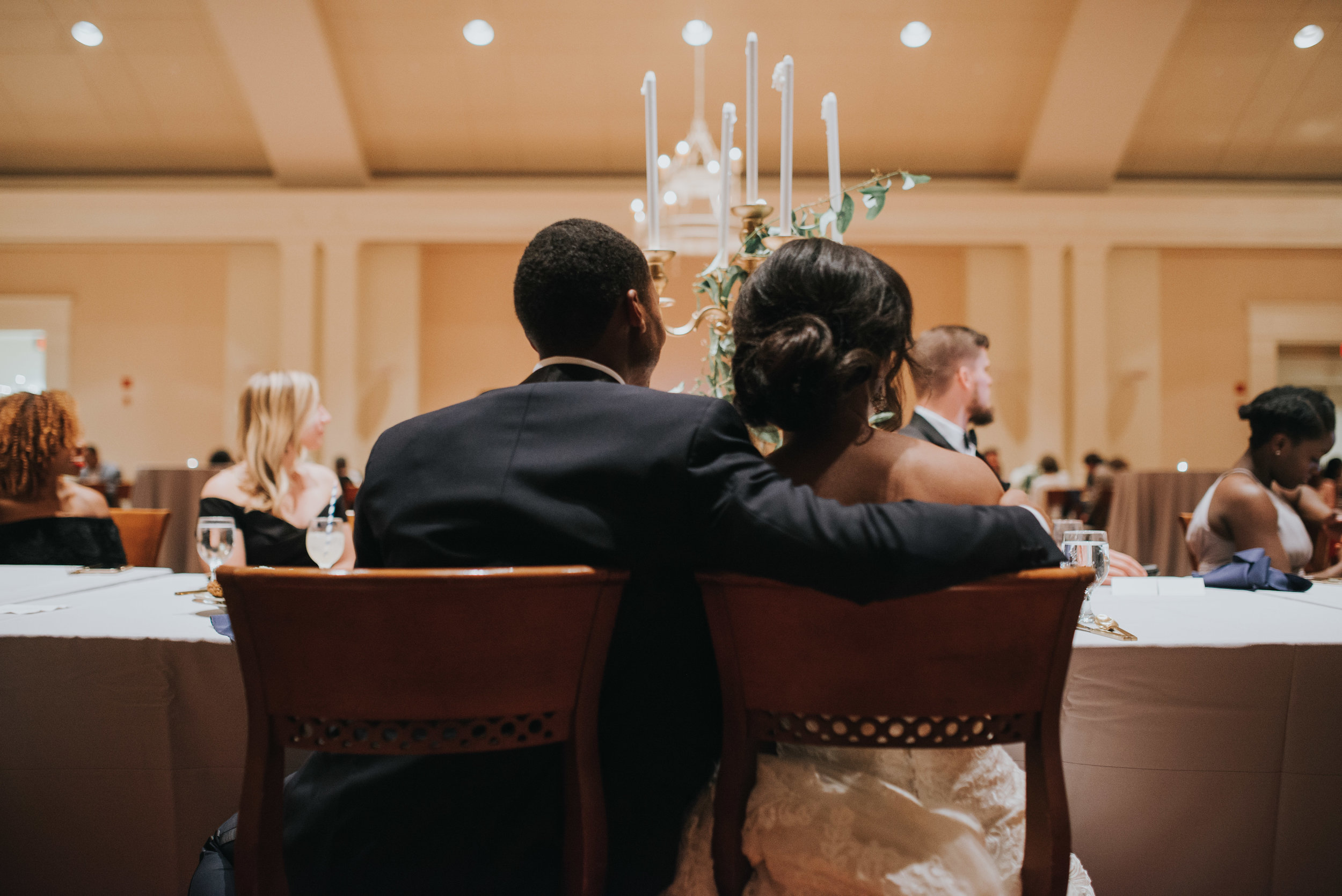 Bride and groom sitting onlooking during toasts