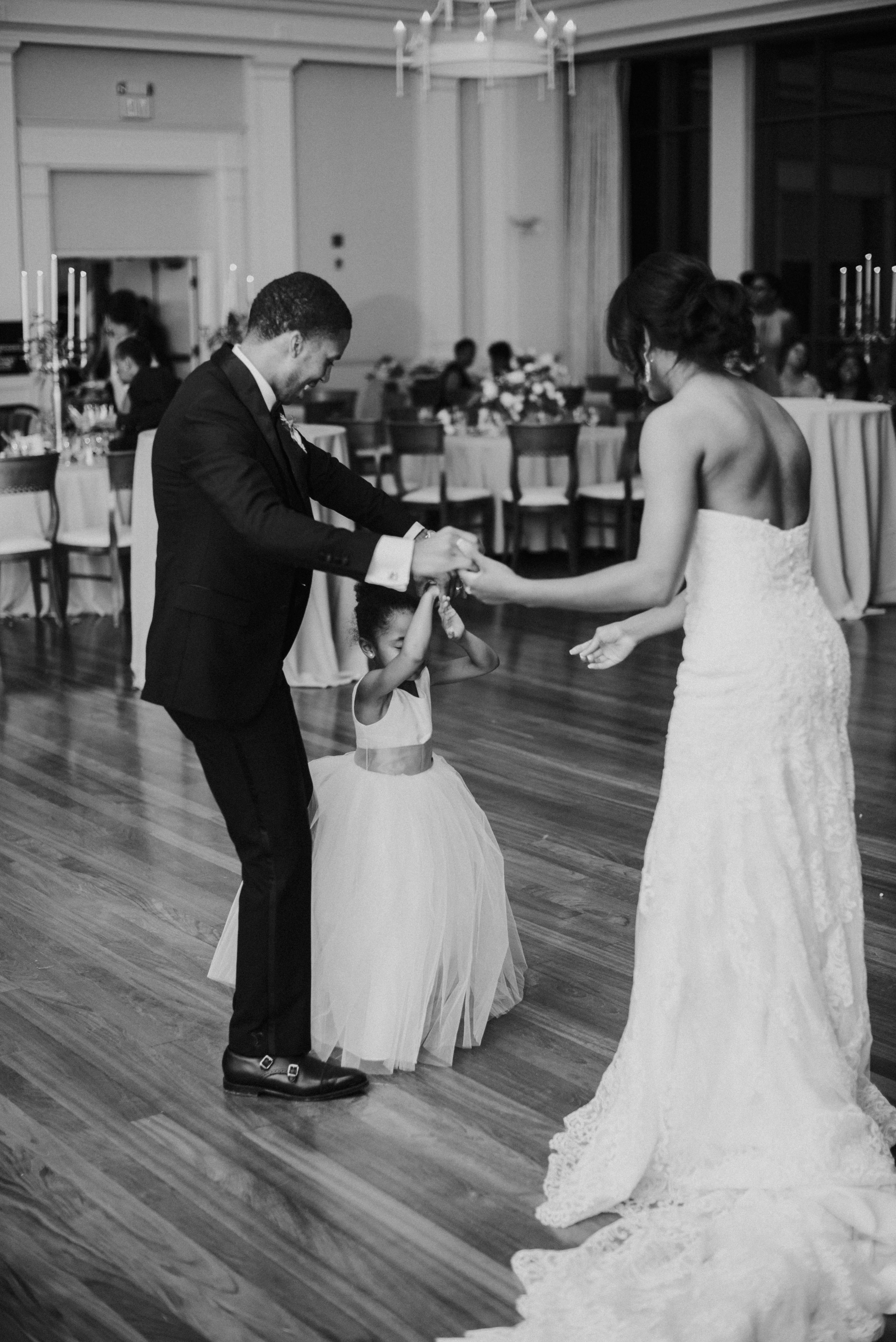 Newlyweds dance with flower girl as a family