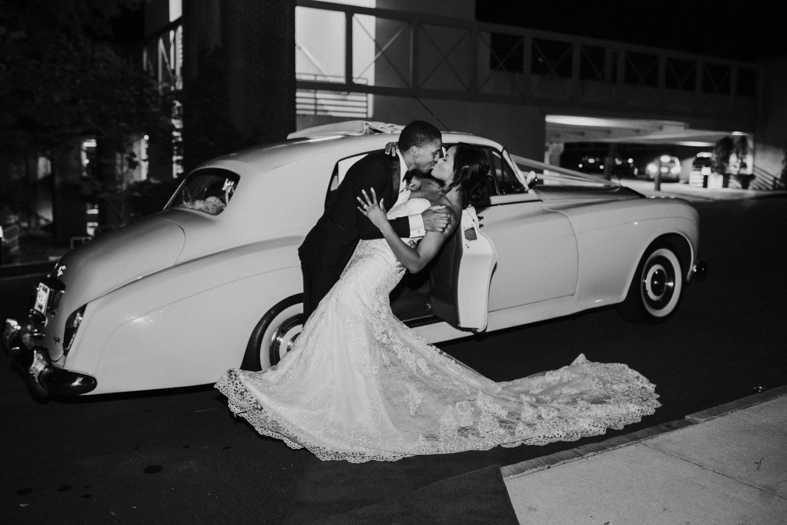 Bride and groom kiss in front of vintage car