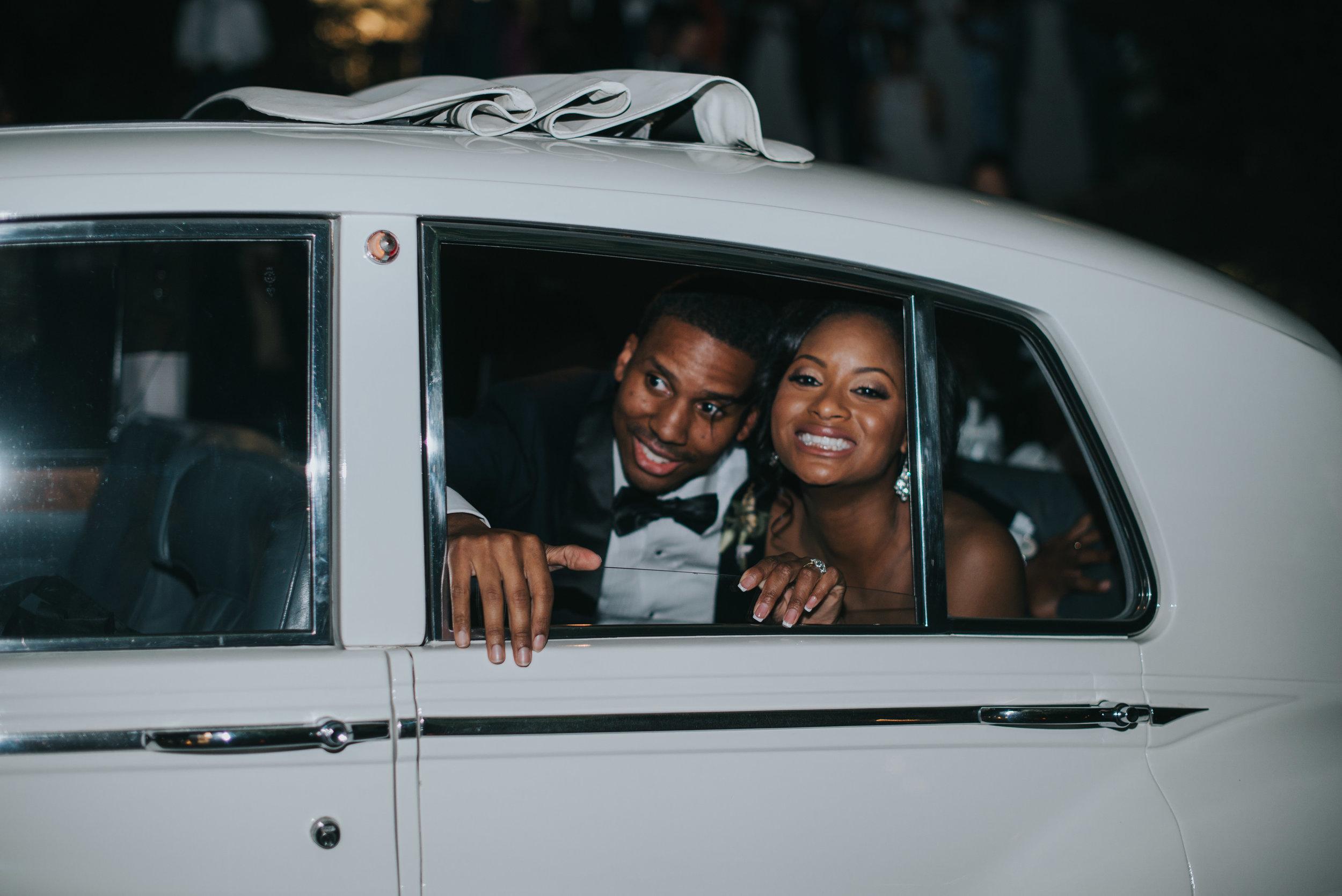 Bride and groom smiling in vintage car