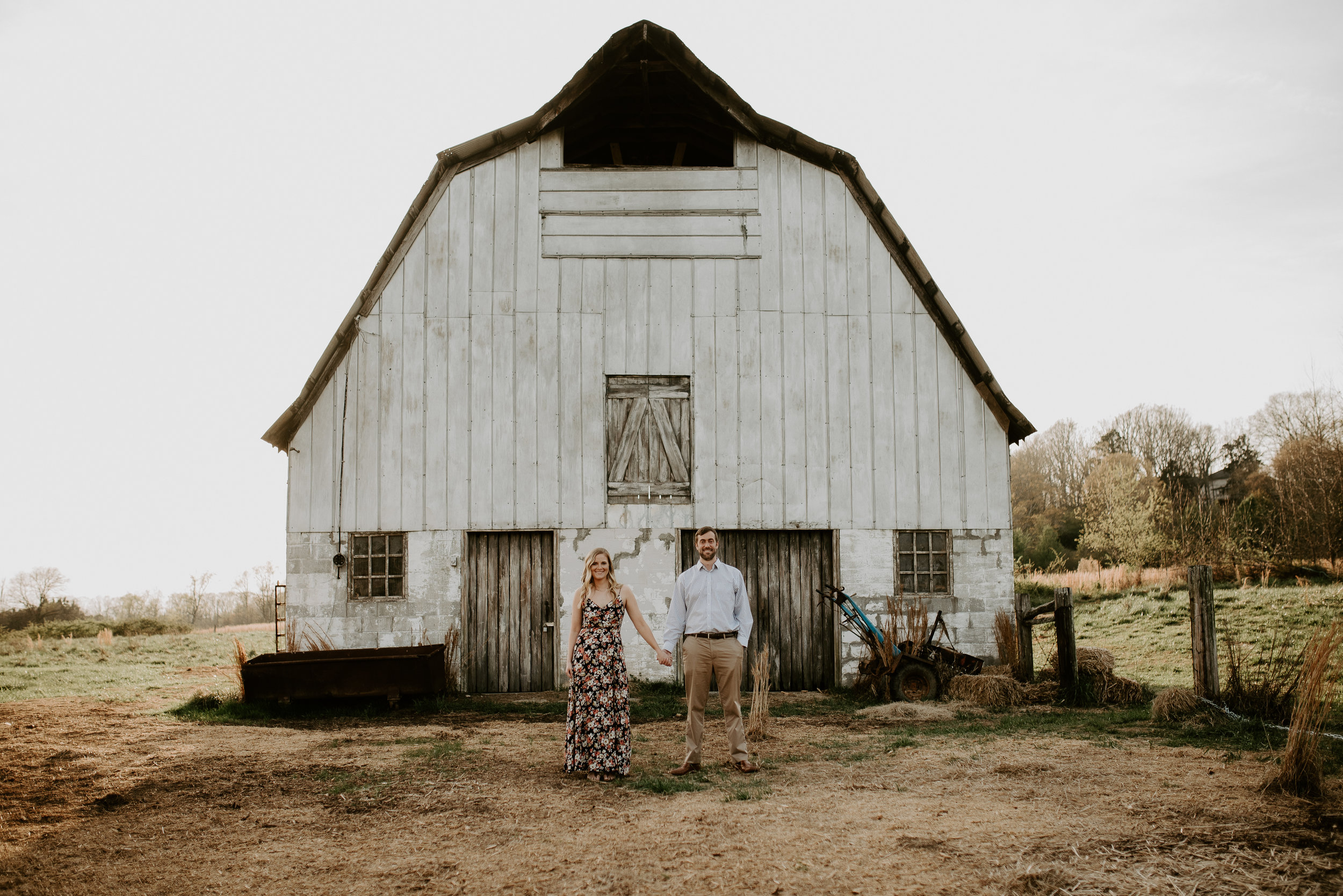 couple standing in front of large barn at arabia mountain engagement session