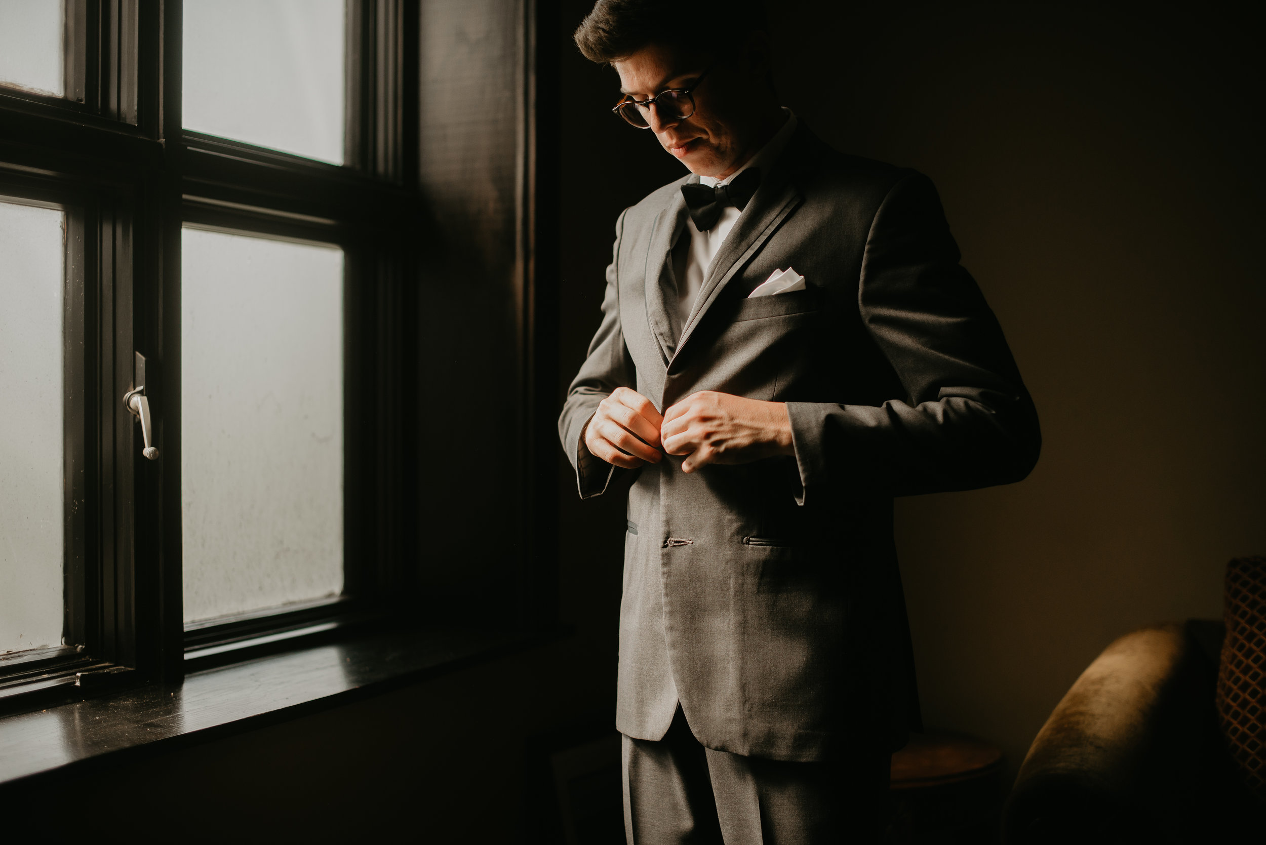 Groom buttoning suit jacket before wedding