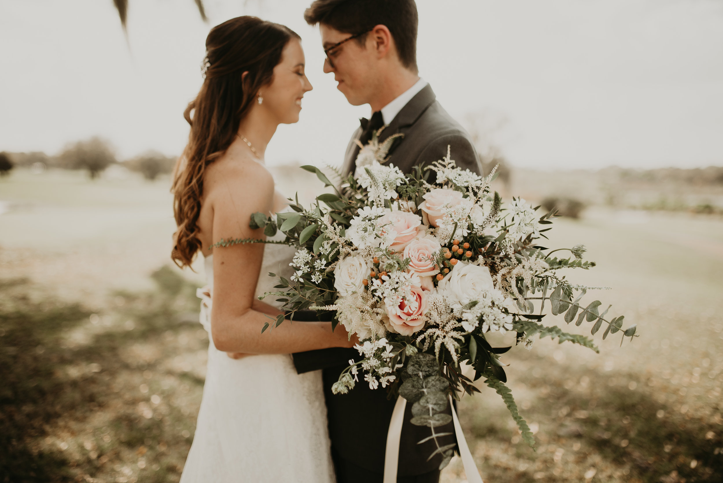 Bride and groom intimate with overgrown wildflower bouquet
