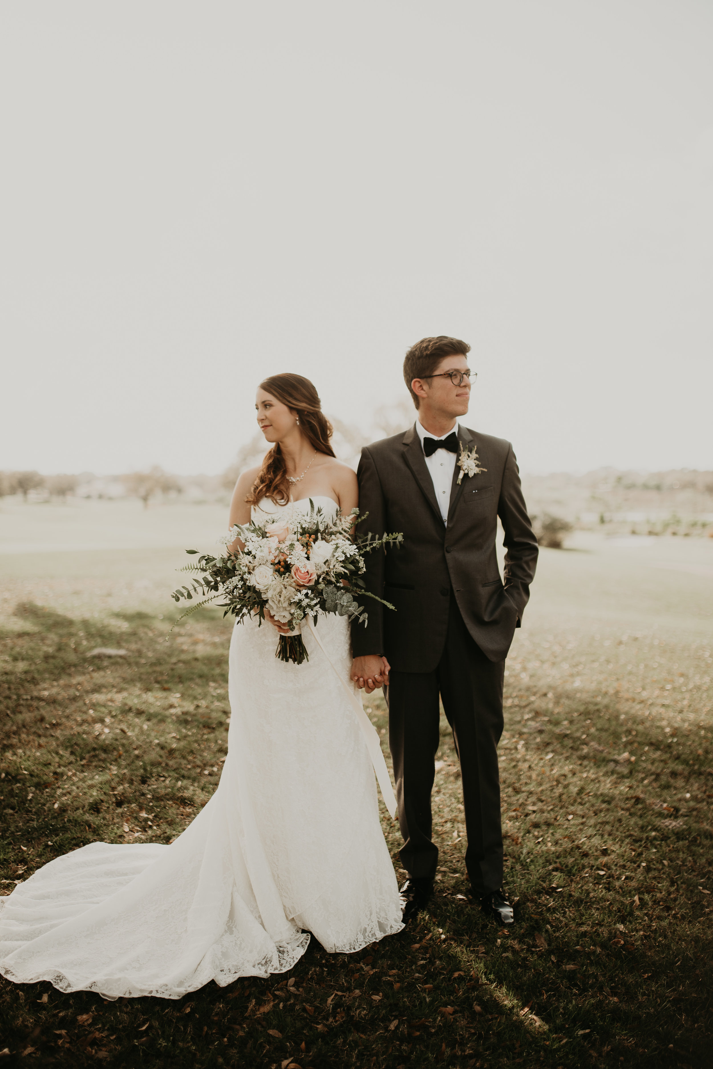 Bride and groom portrait with large wildflower bouquet