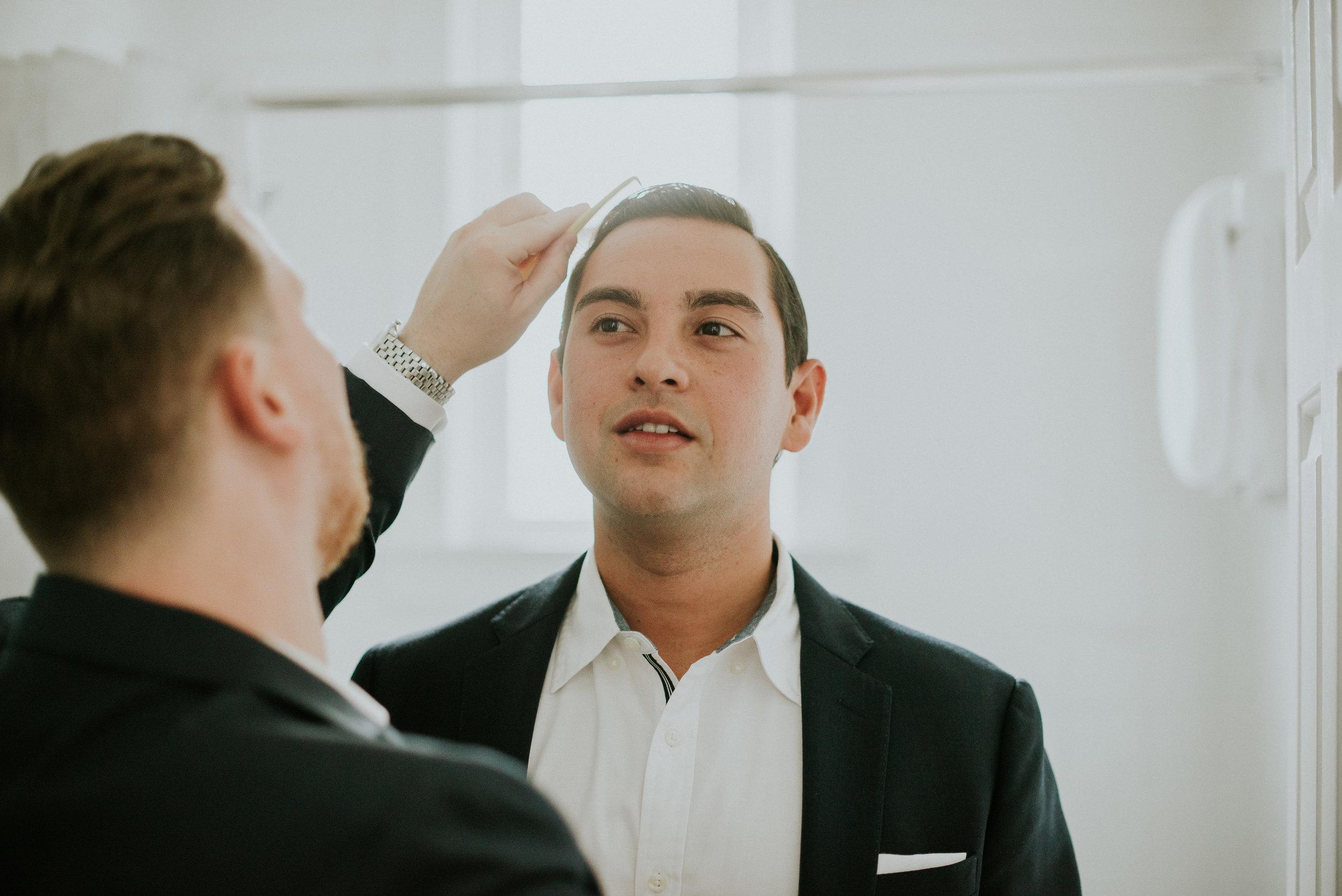 Groomsman combing groom's hair before wedding
